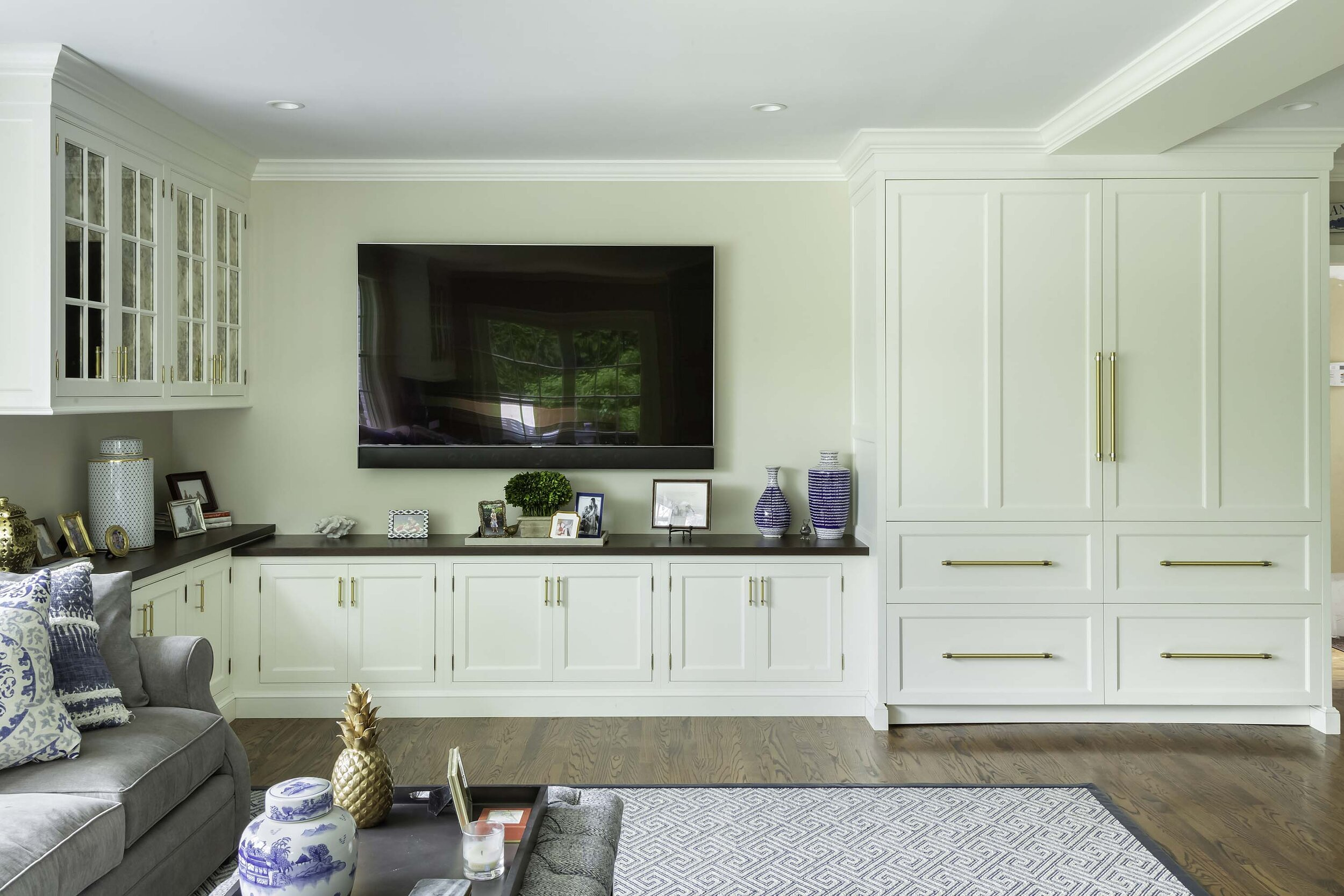 Custom storage in family room with espresso-stained counter with Sub Zero refrigerator/freezer