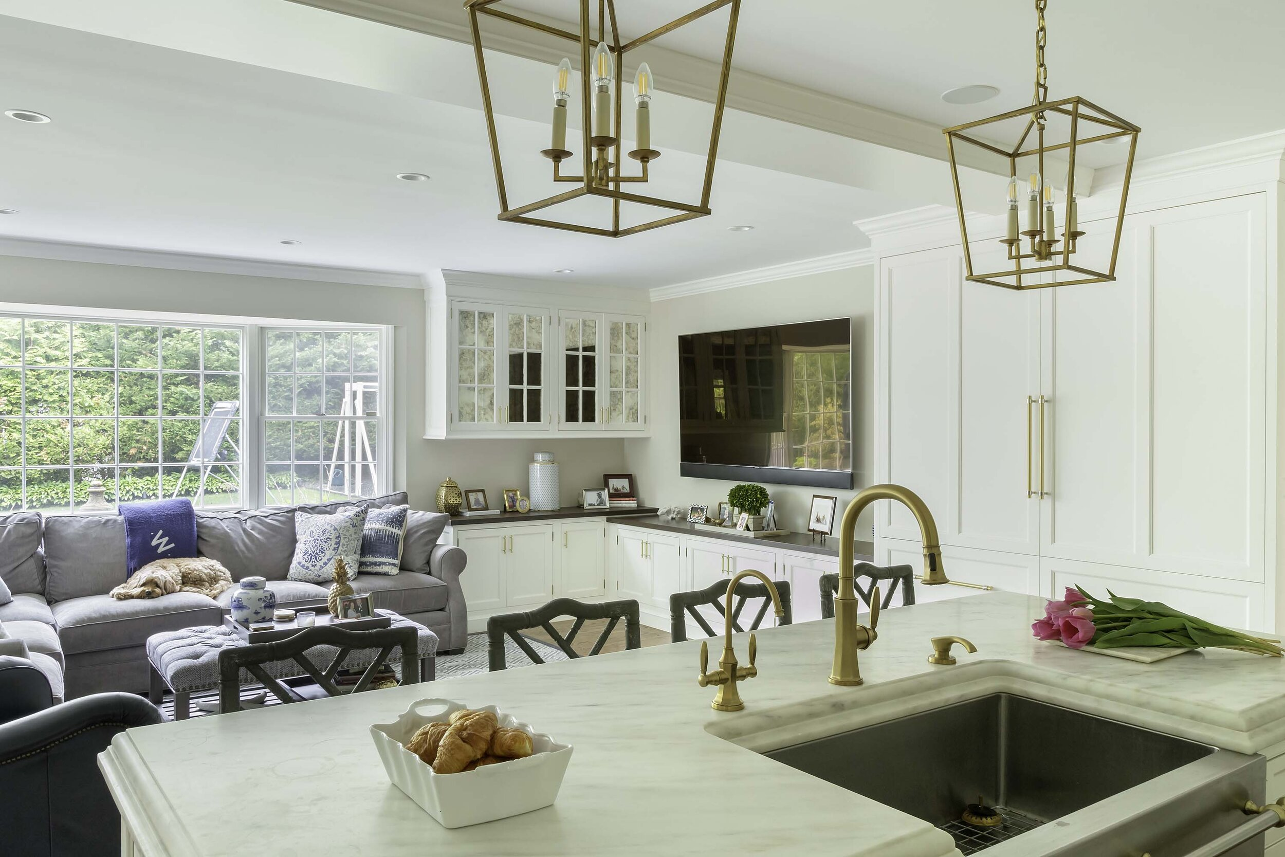 Transitional white kitchen with beautiful Danbe marble countertop is open to the family room
