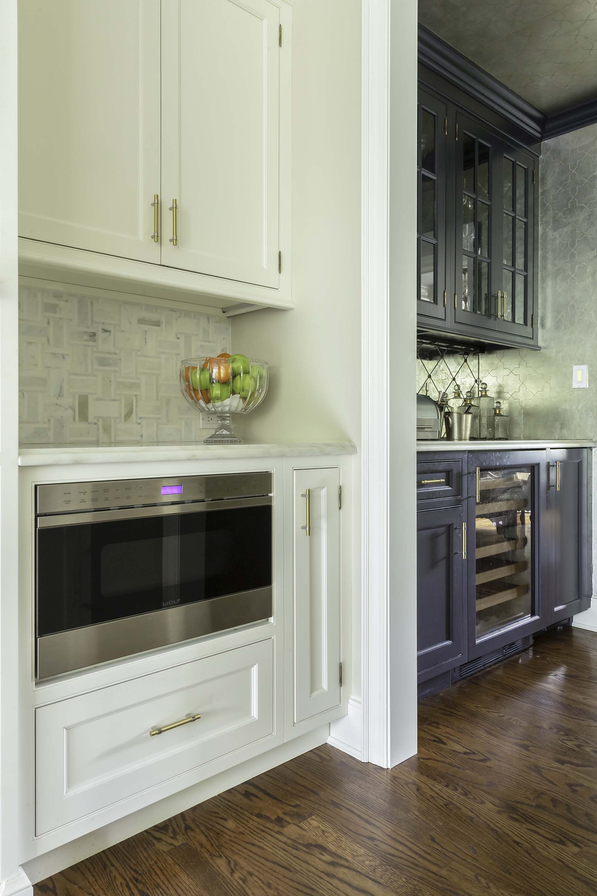 Transitional white kitchen and formal dining connected by the butler's pantry with Sub Zero wine cooler and Wolf microwave