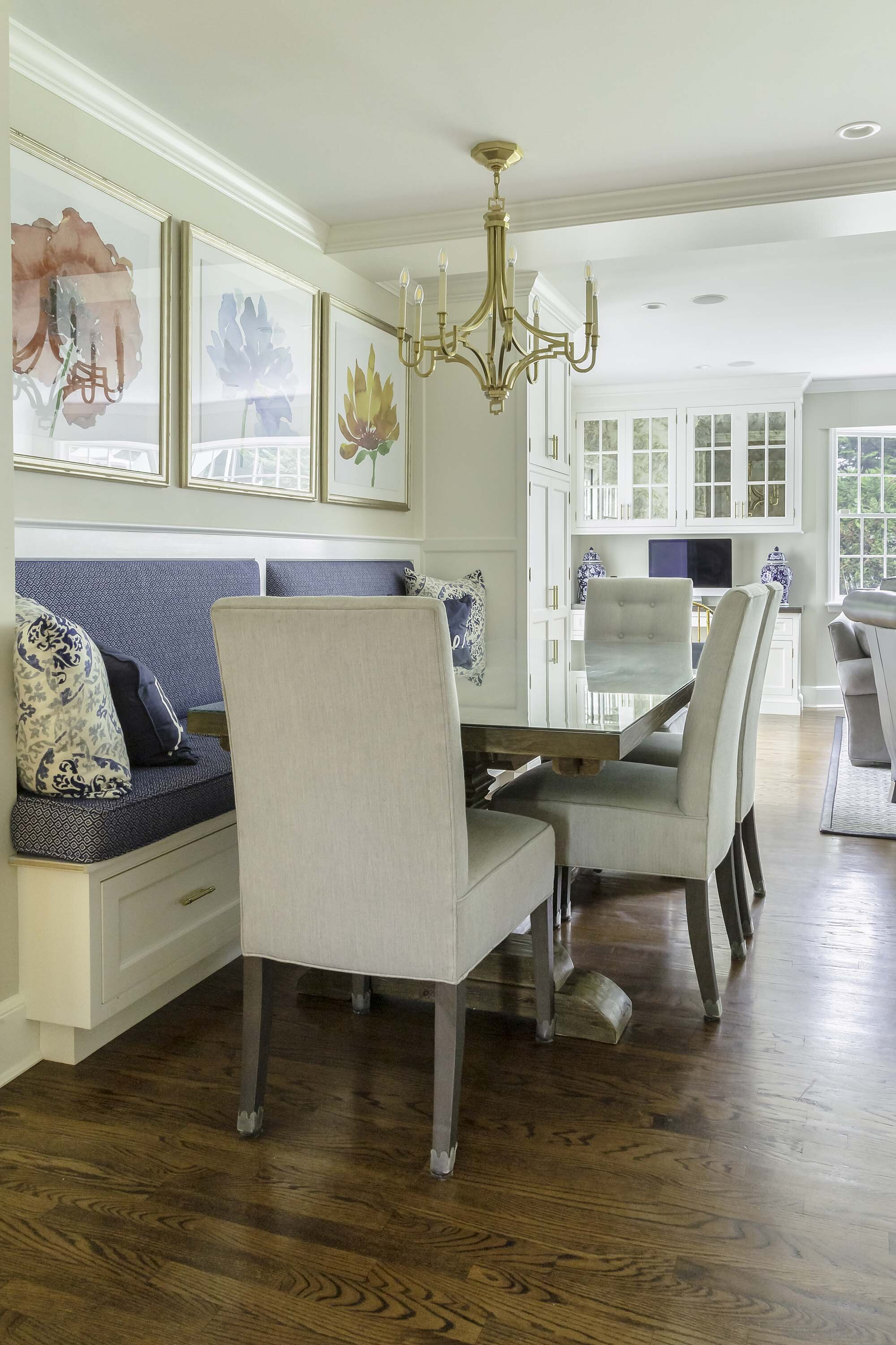 Custom banquette with storage drawers add extra seating in dining area