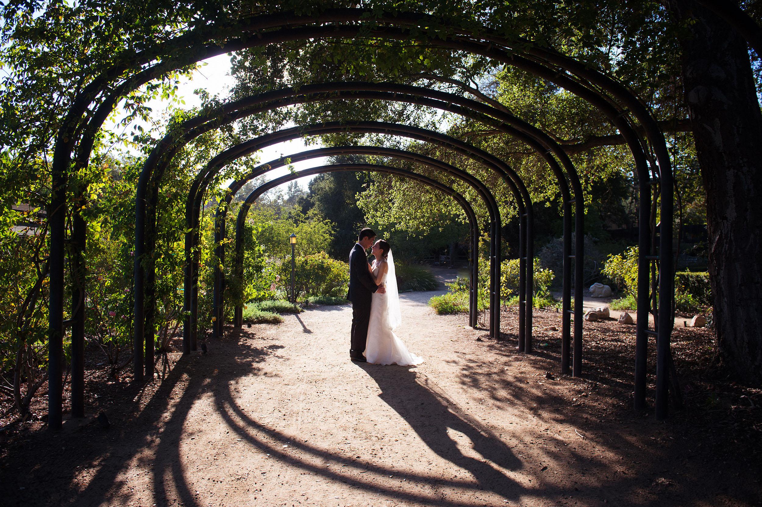 Bride and groom kissing under archway at Descanso Gardens in La Canada Flintridge.