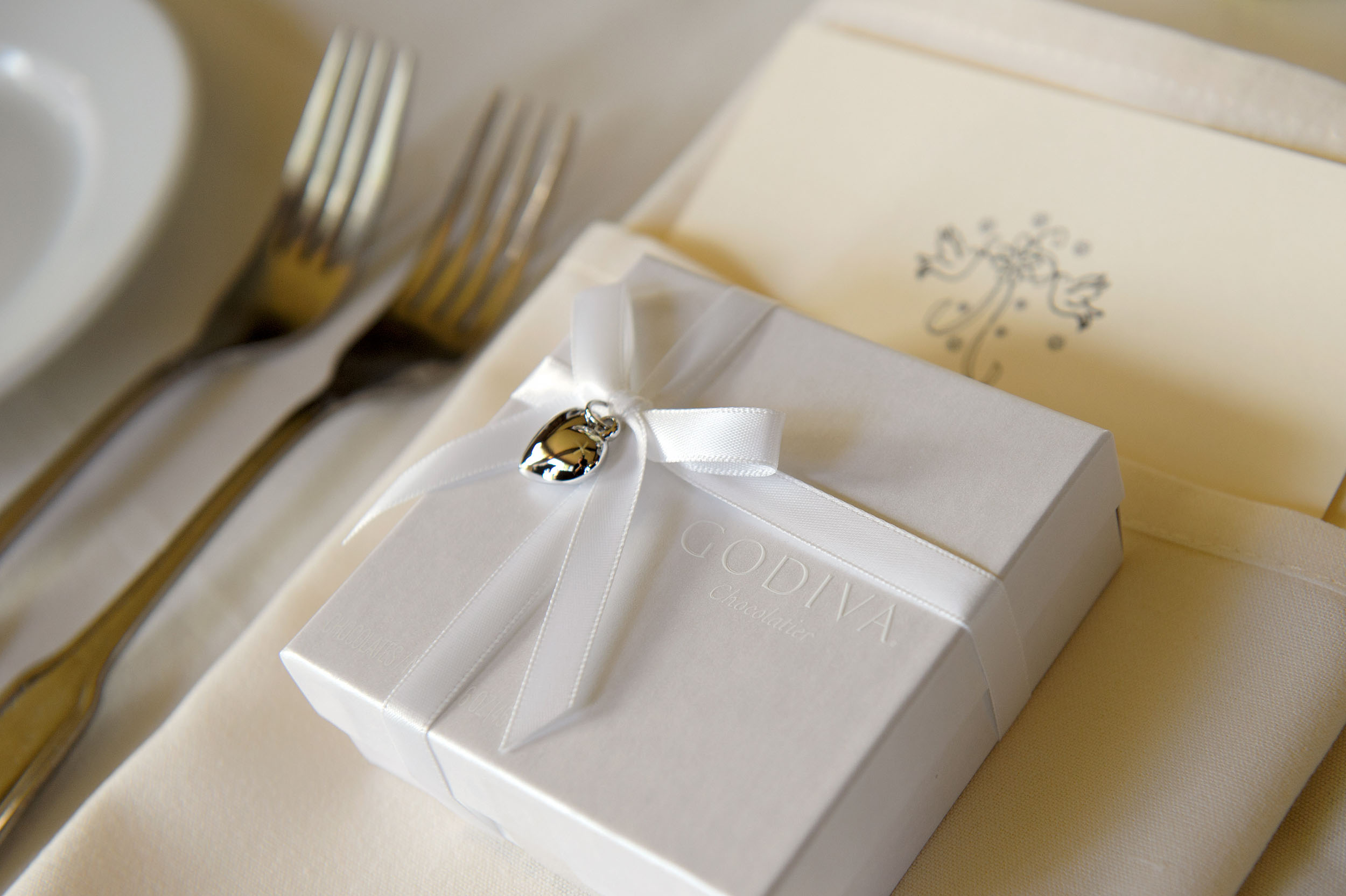 A white Godive Chocolate box with ribbon and heart charm wedding reception place setting.