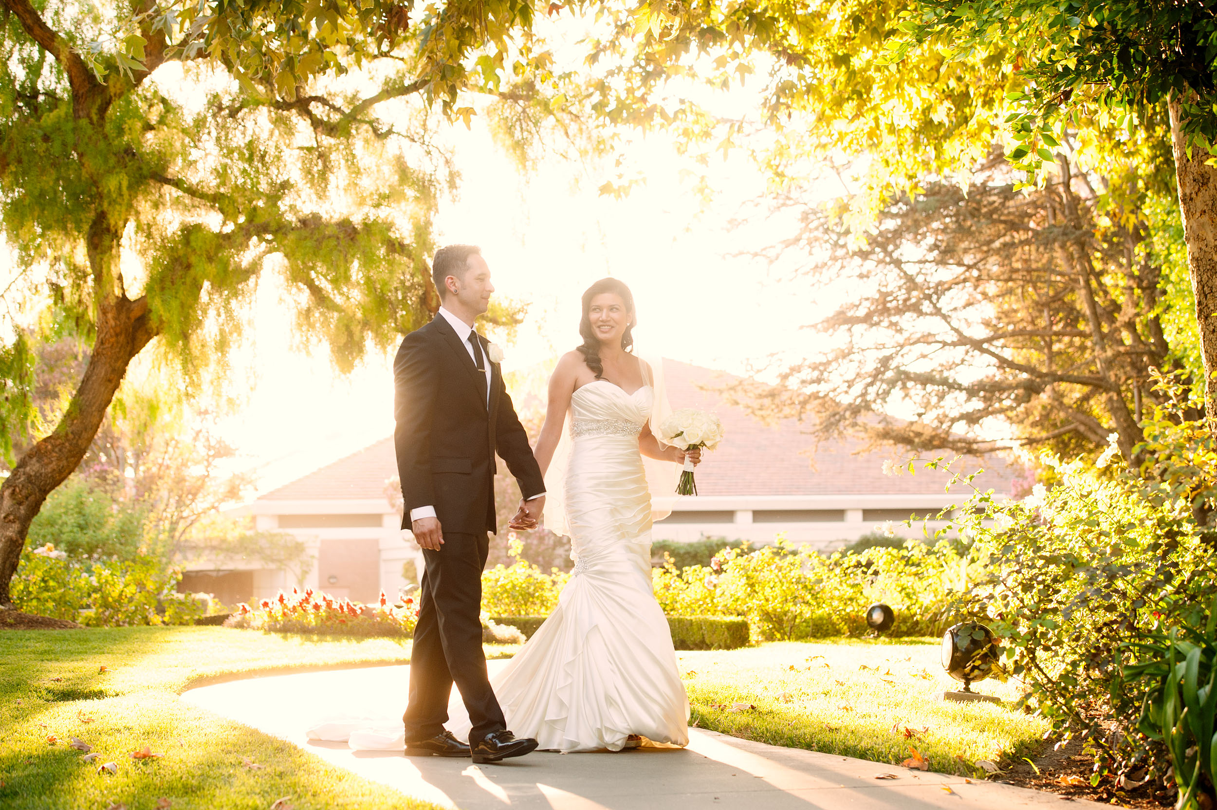 A bride and groom walk bathed in sunlight at the Nixon Presidential Library & Museum in Yorba Linda.