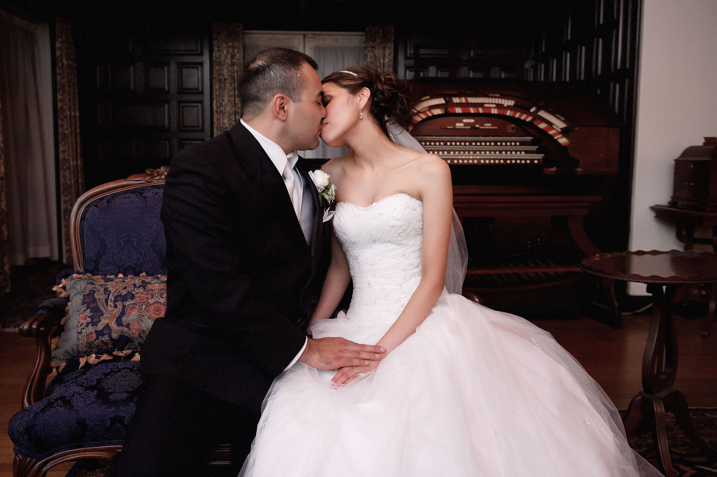 Bride and groom kissing in front of antique piano at the Kellogg House at Cal Poly Pomona.