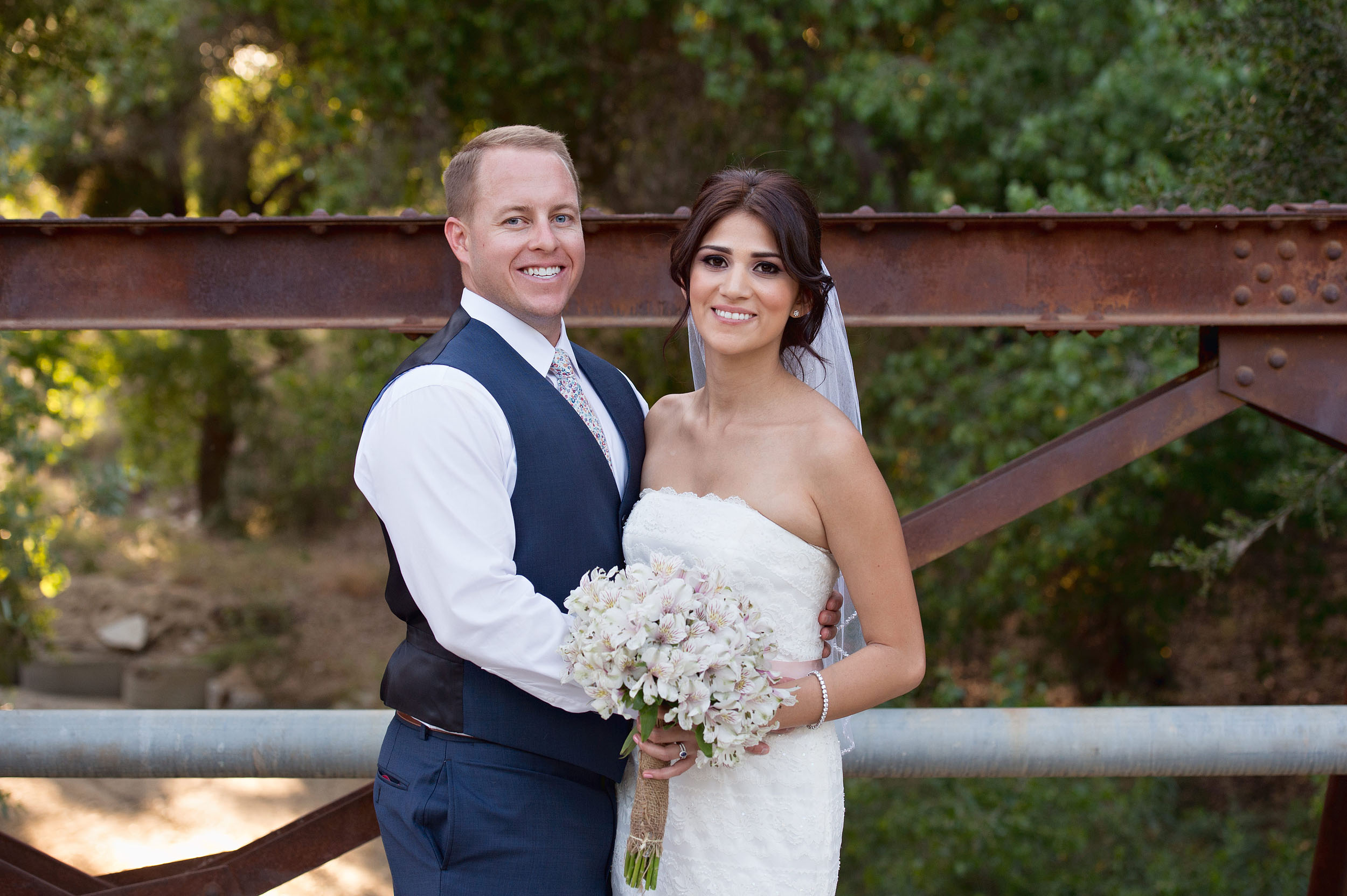Bride and groom on bridge at Ollis Ranch in Redlands.