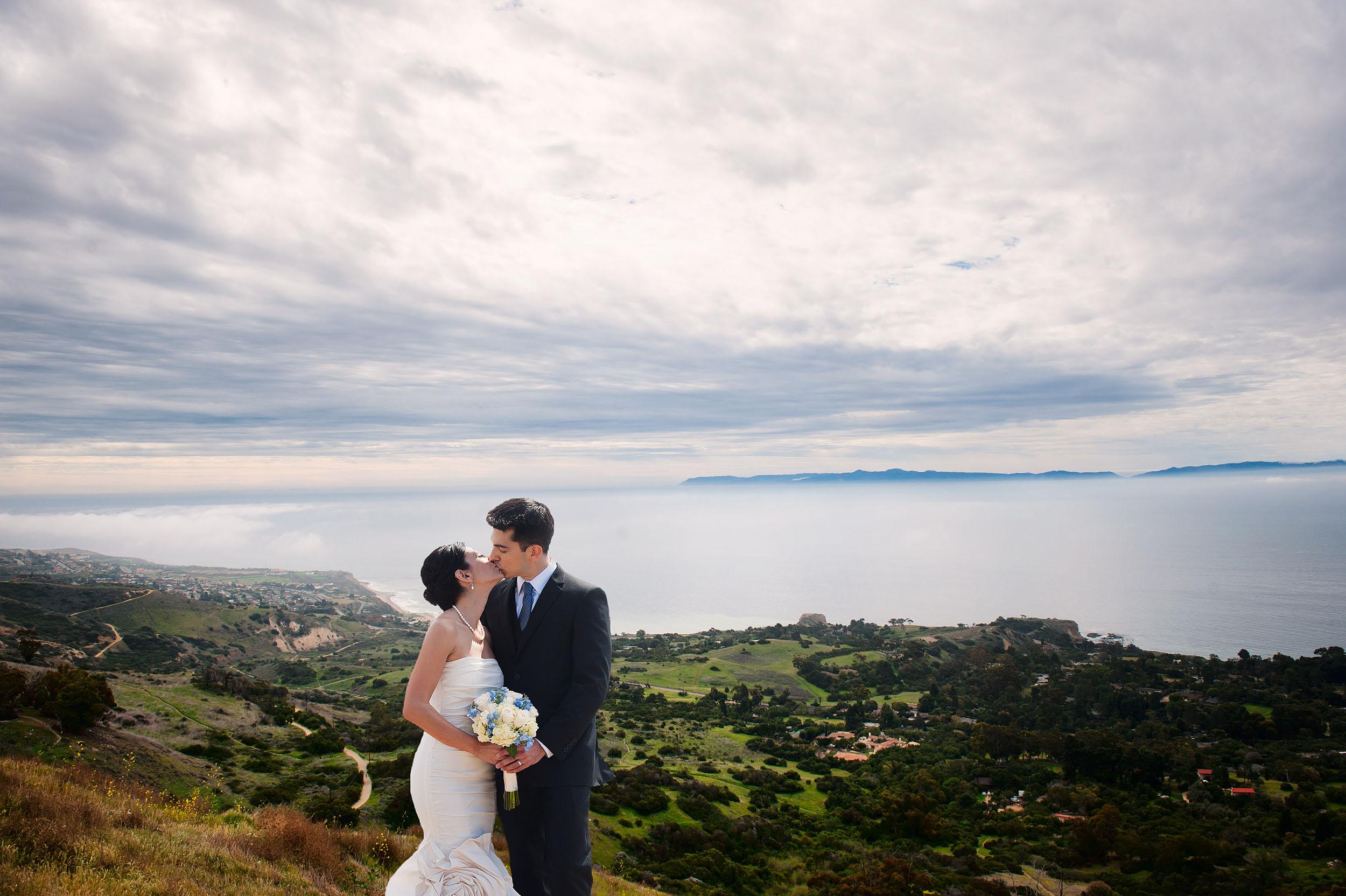 Bride and groom kissing, at Del Cerro Park overlooking Rancho Palos Verdes.