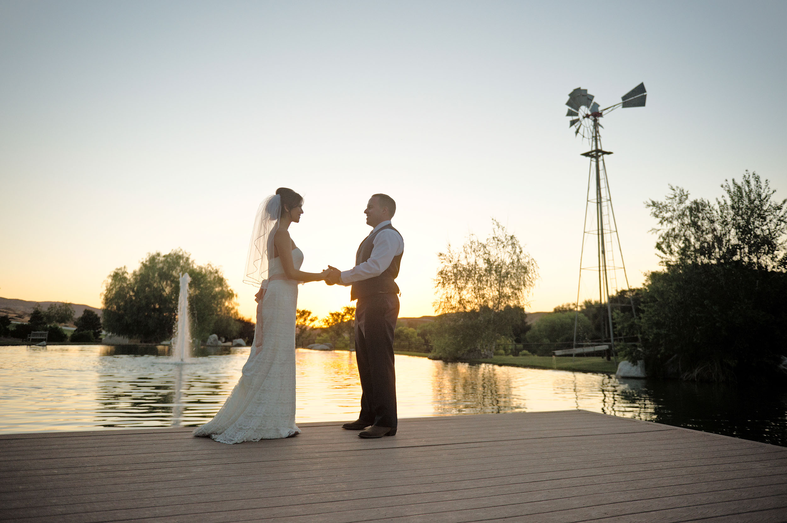 Bride and groom at sunset at lake at Ollis Ranch in Redlands.