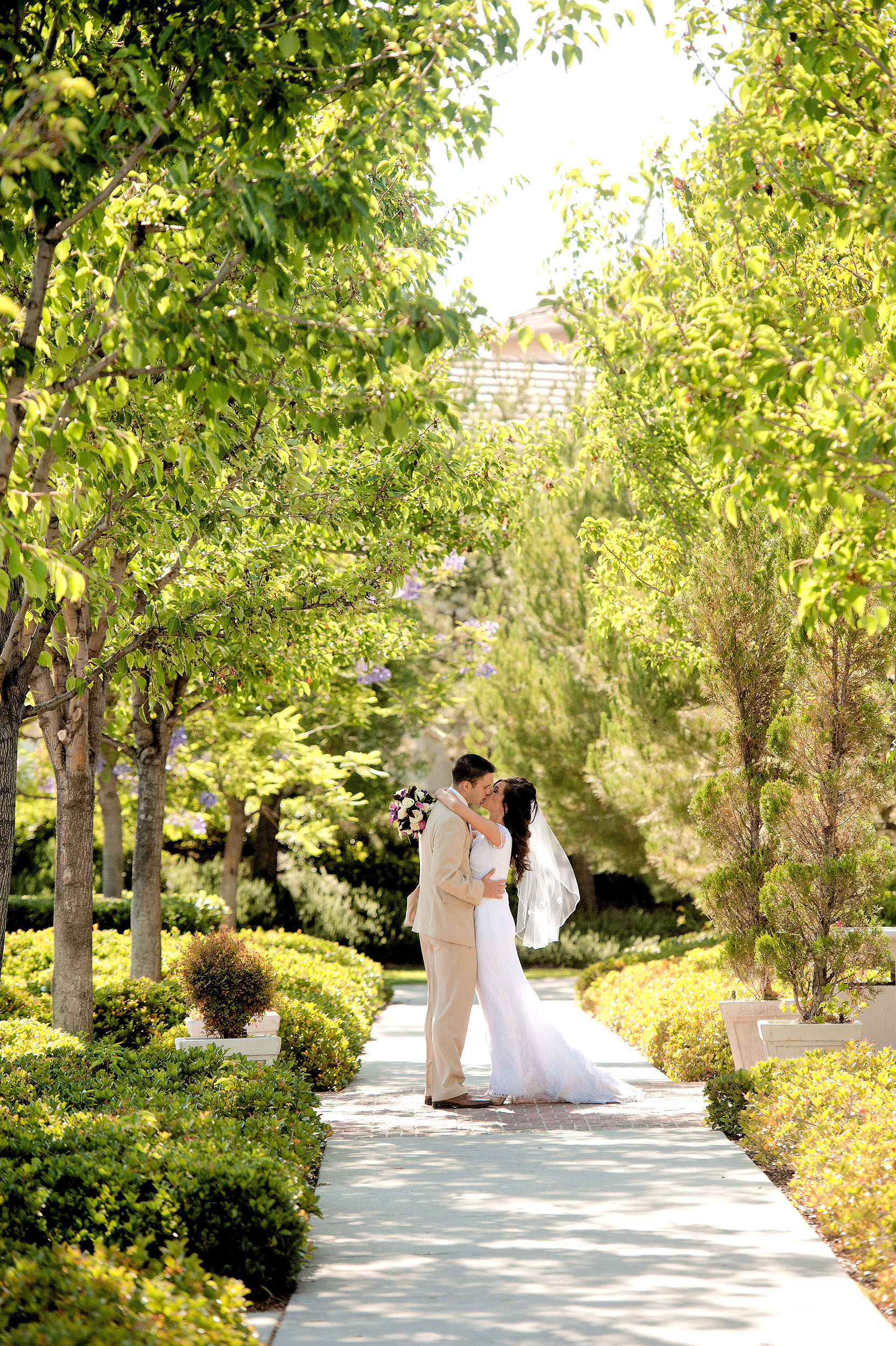 Bride and groom kissing at Harveston Lake Park in Temecula.