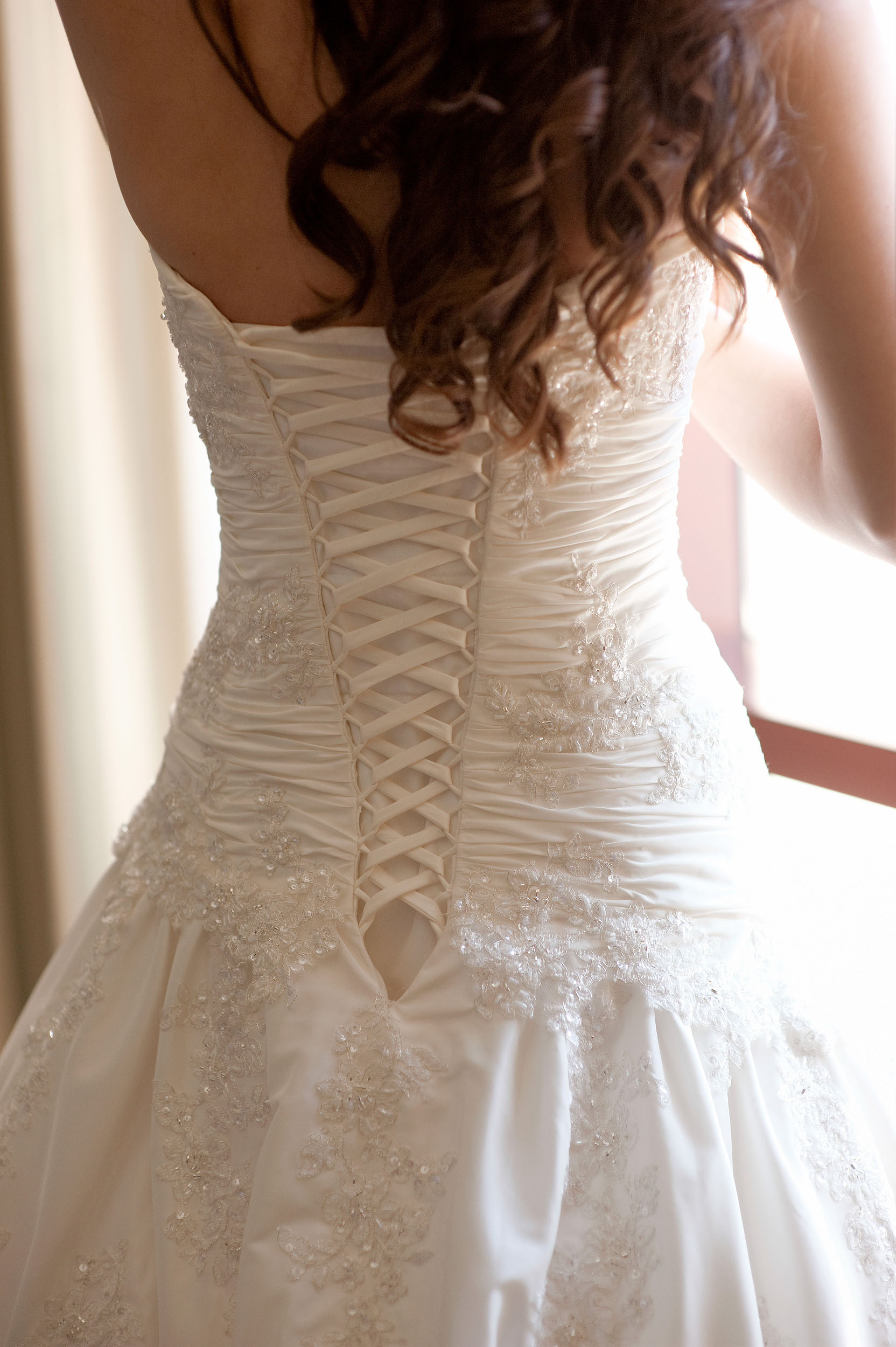 Lacing on back of bride's wedding dress at Pechanga Resort & Casino in Temecula.