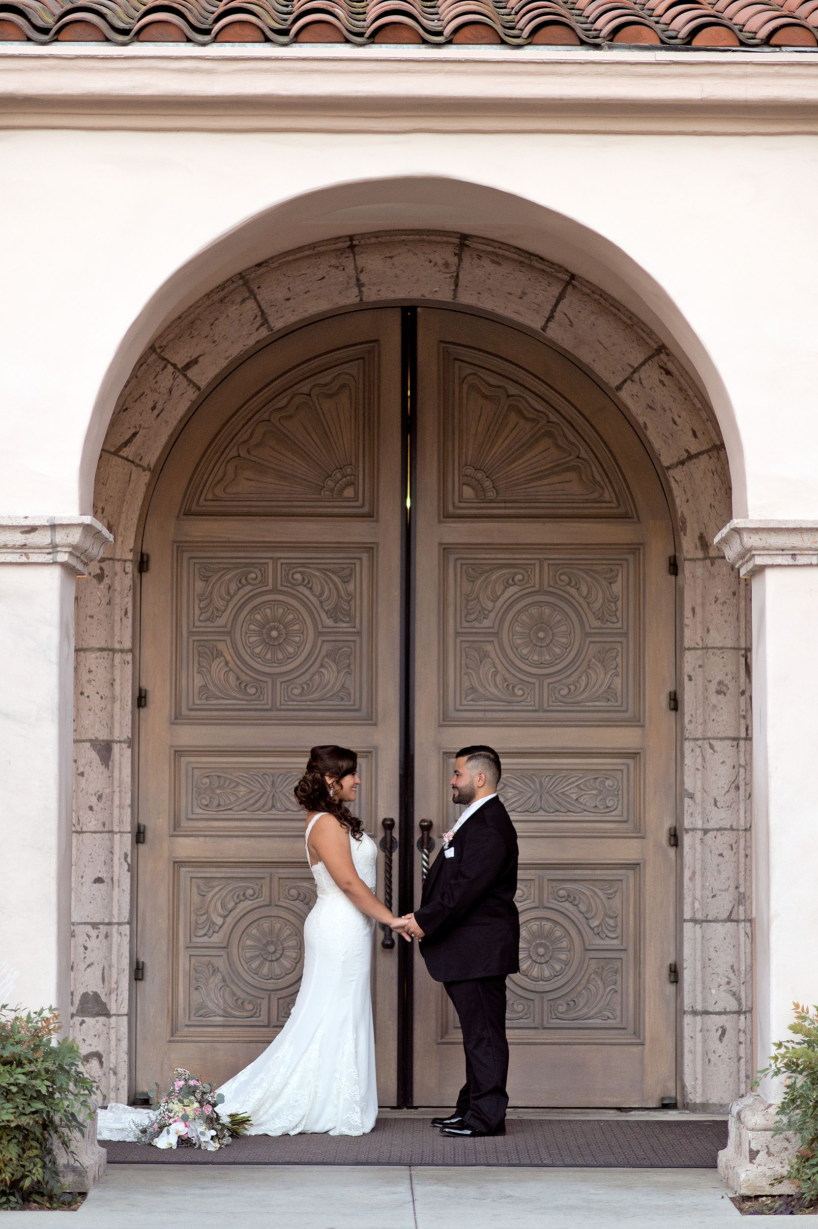 Bride and groom facing each other in front of large arched double doorway at St. Denis Catholic Church in Diamond Bar.