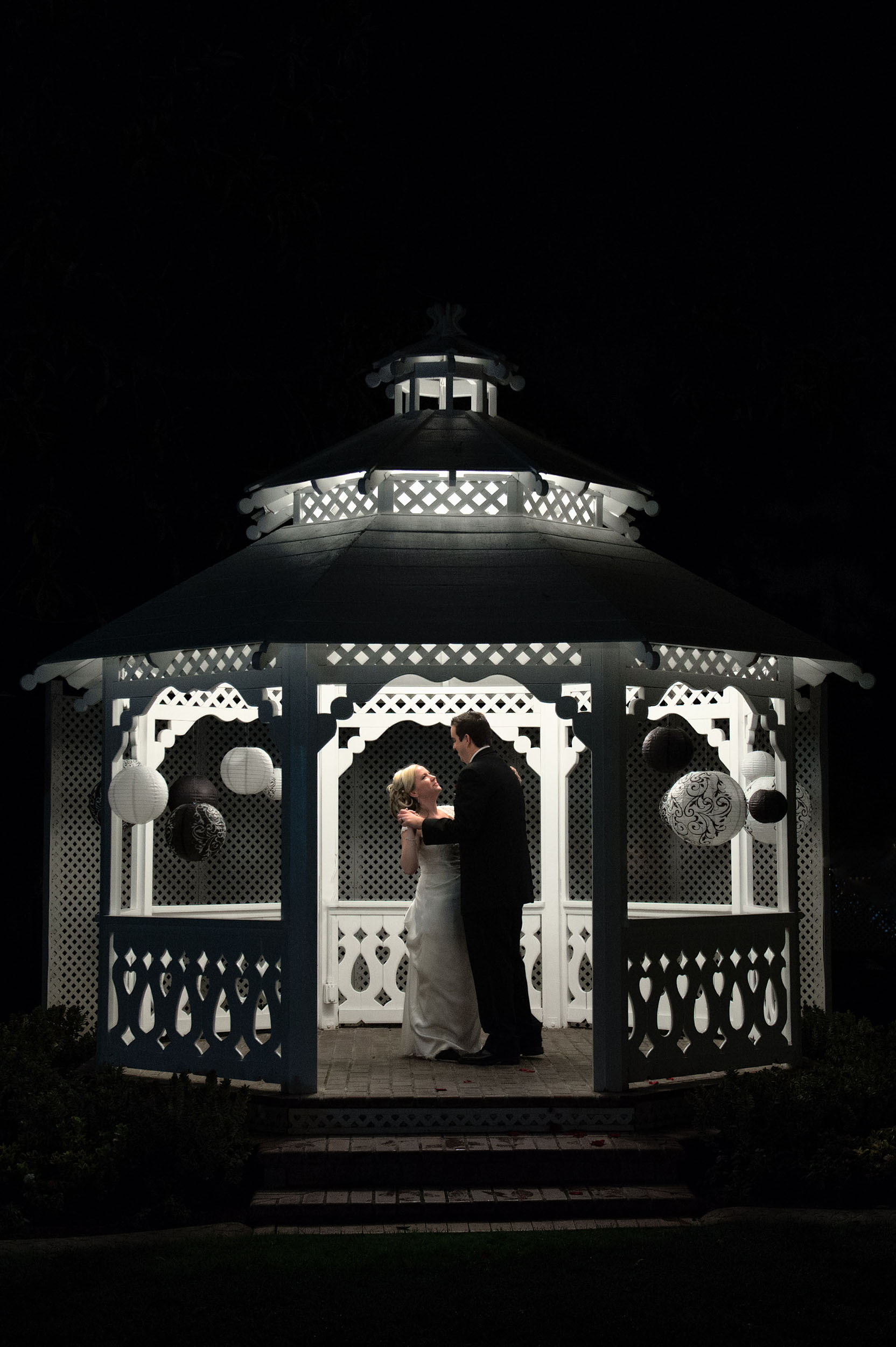Bride and groom dancing at night in gazebo at Alta Vista Country Club in Placentia.