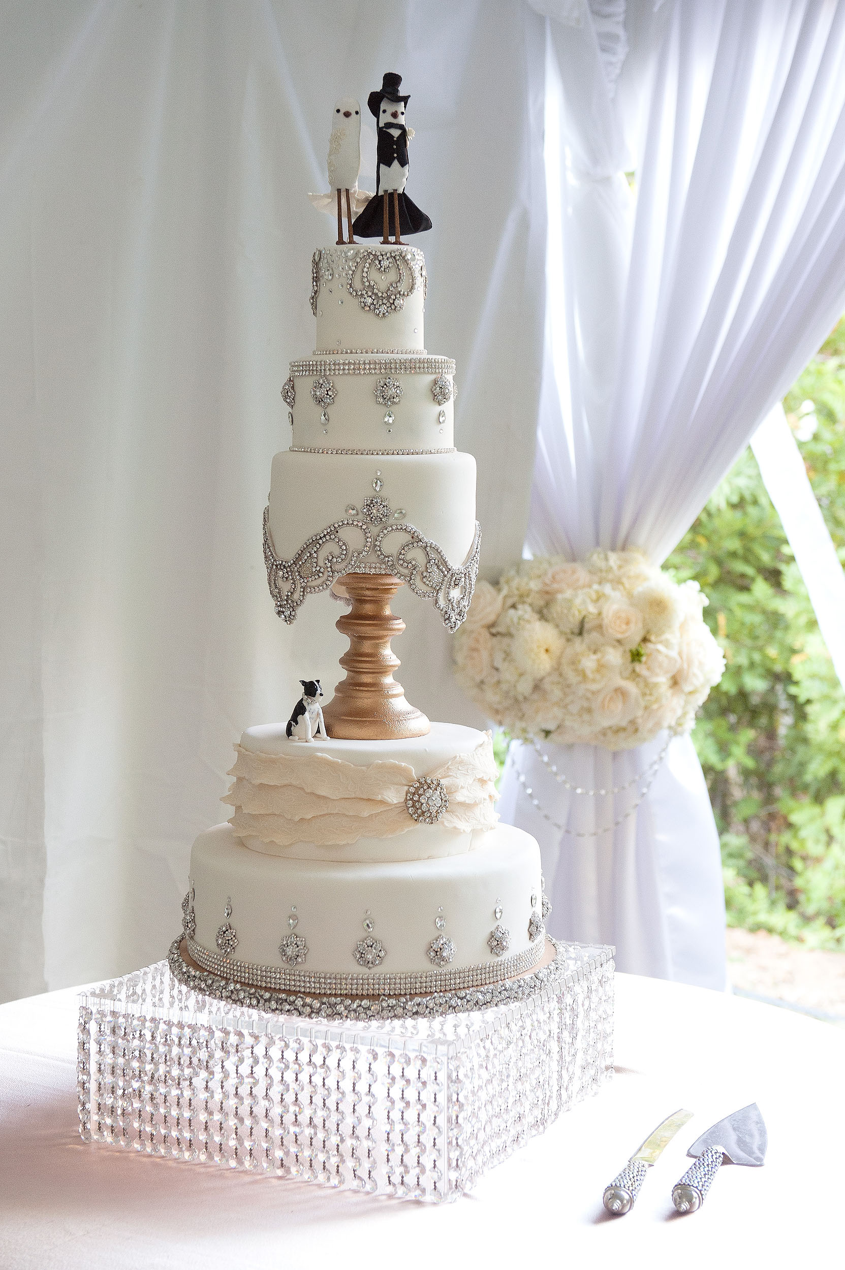 Multi-layer wedding cake with bride and groom topper and dog.