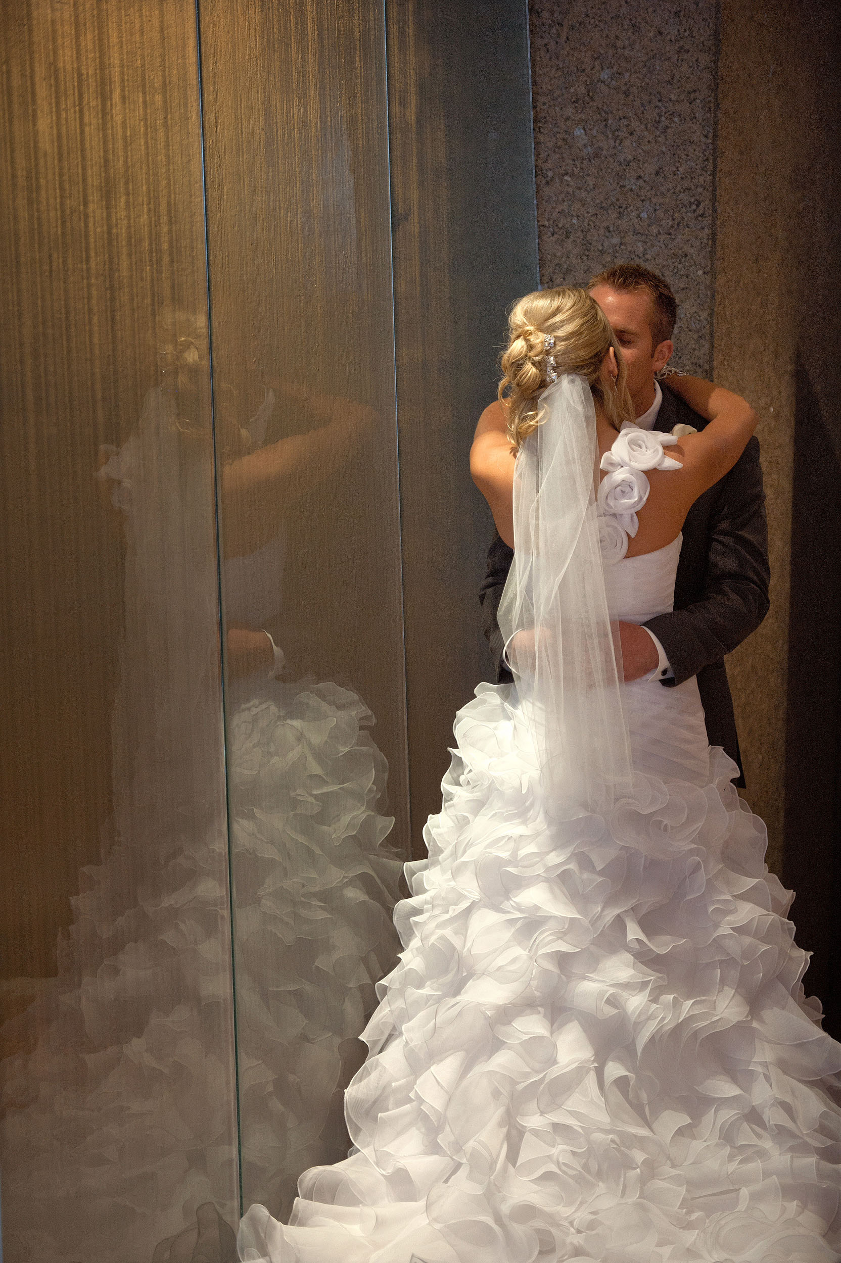 Bride and groom by glass wall at Seven-Degrees in Laguna Beach.