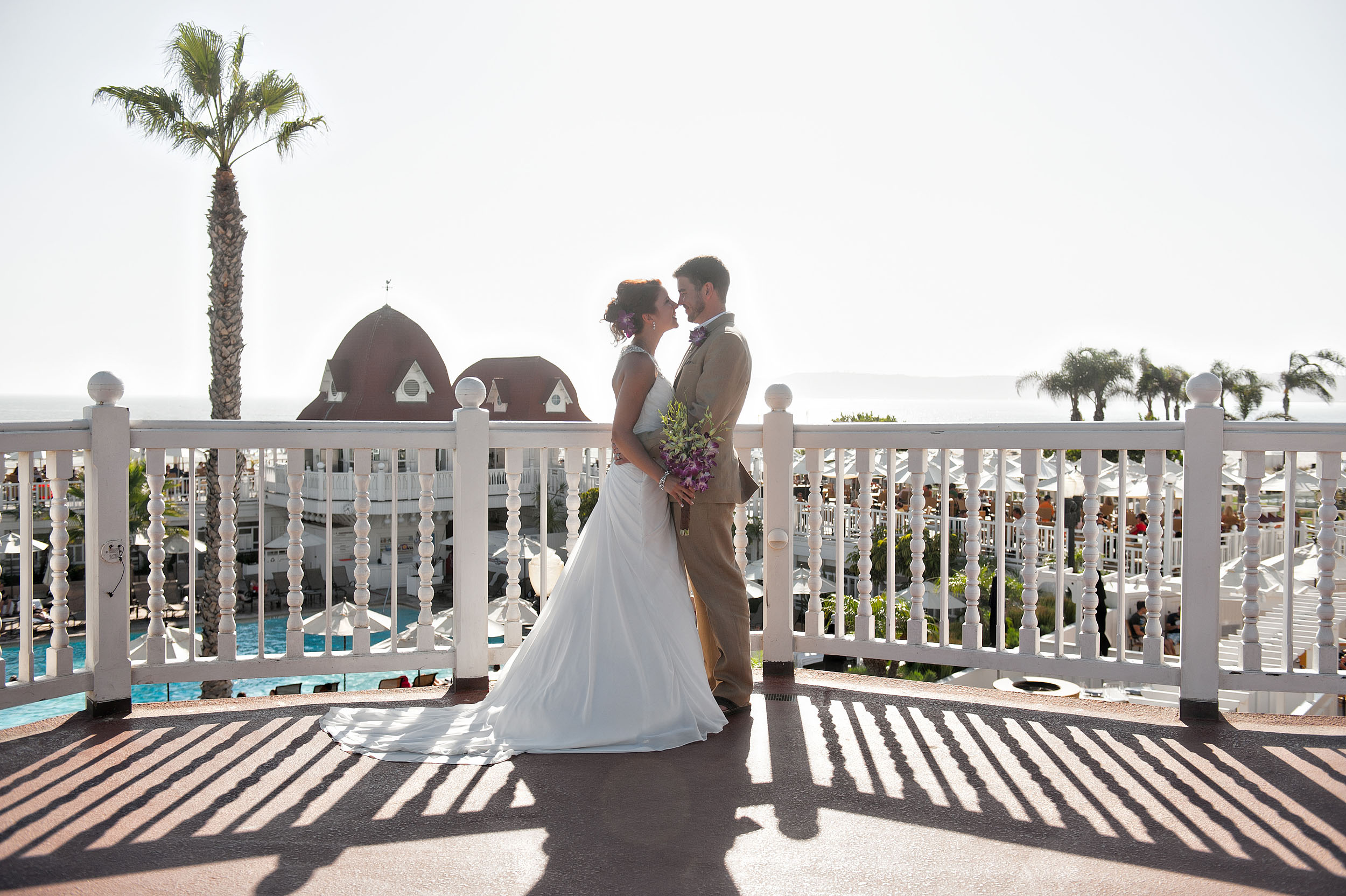 Bride and groom nose to nose on deck of the Hotel del Coronado.