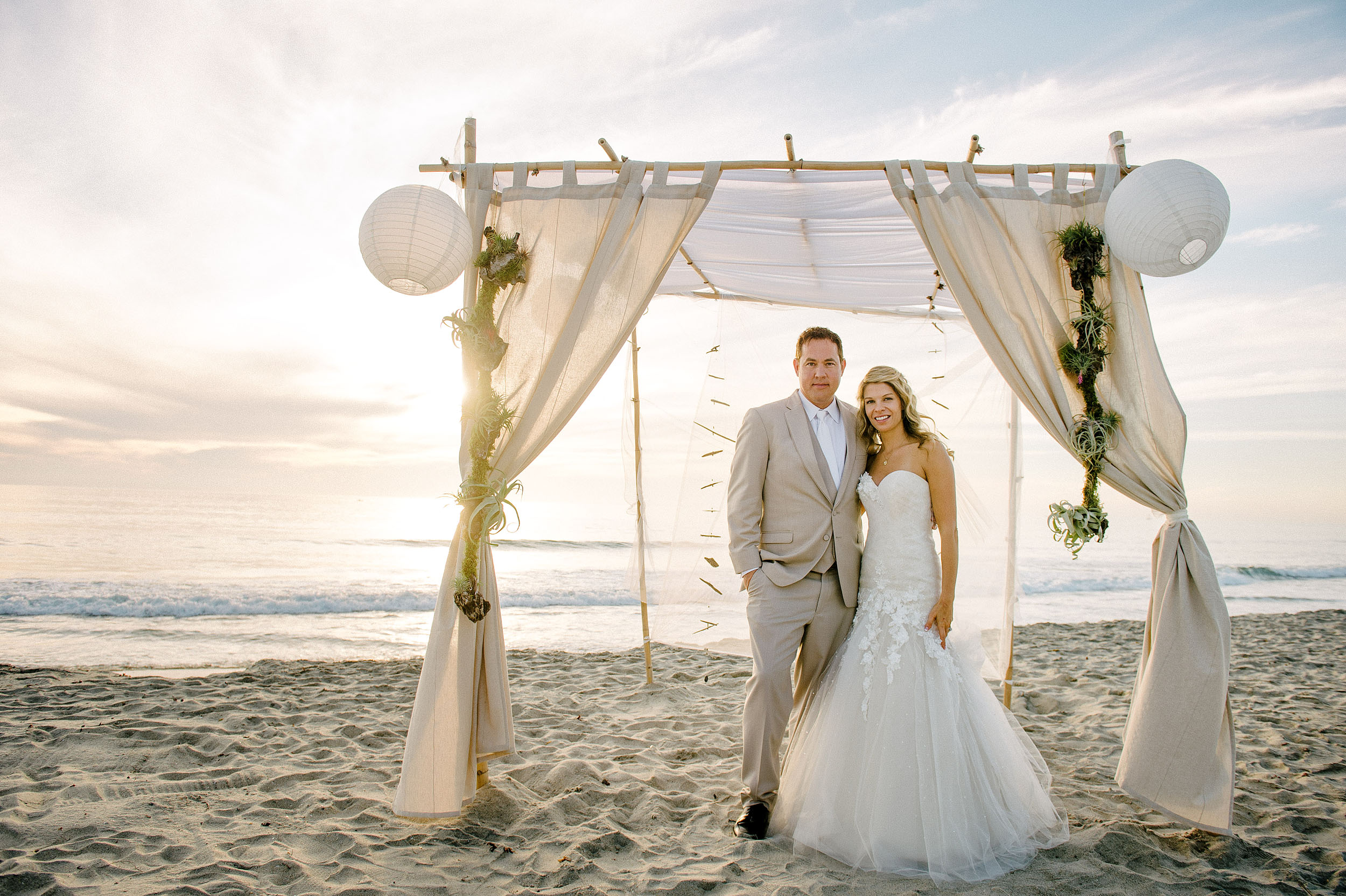 Bride and groom on beach at sunset in Oceanside.