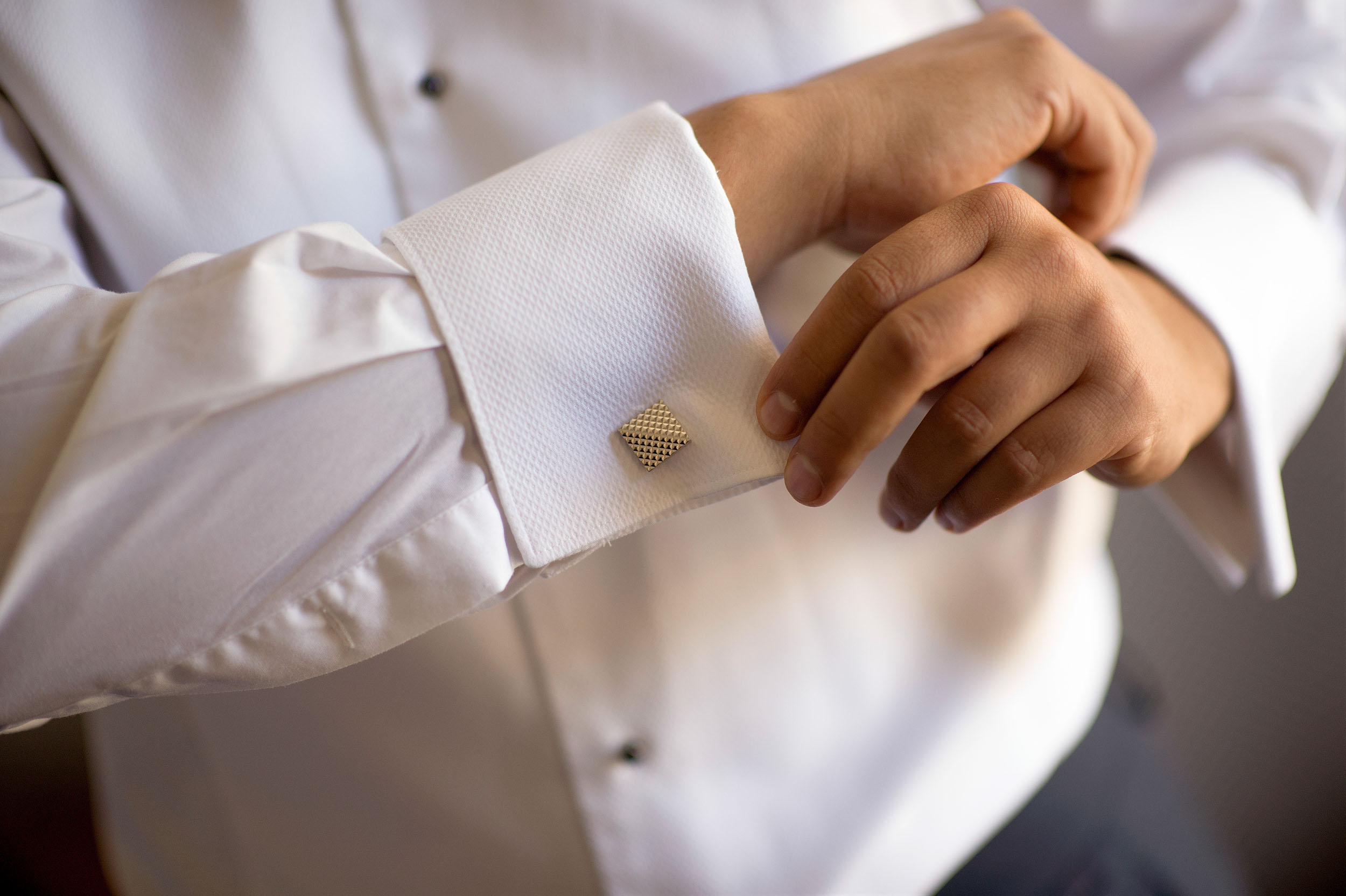 Groom putting on cufflinks while getting ready for wedding.