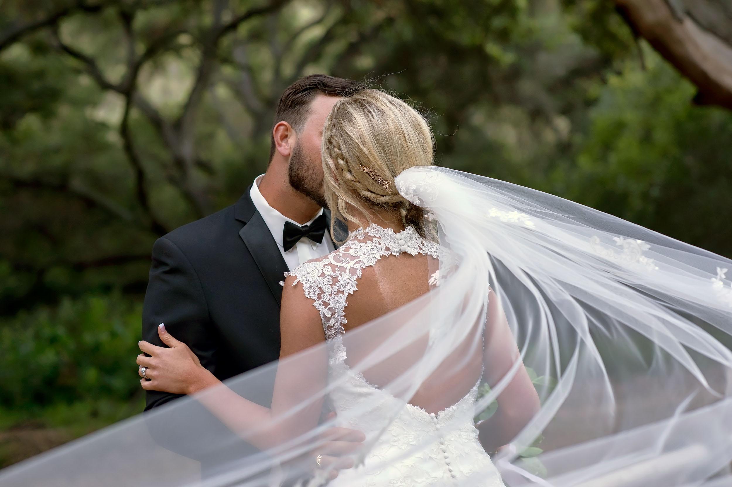 Bride and groom with flowing veil at Temecula Creek Inn in Temecula.