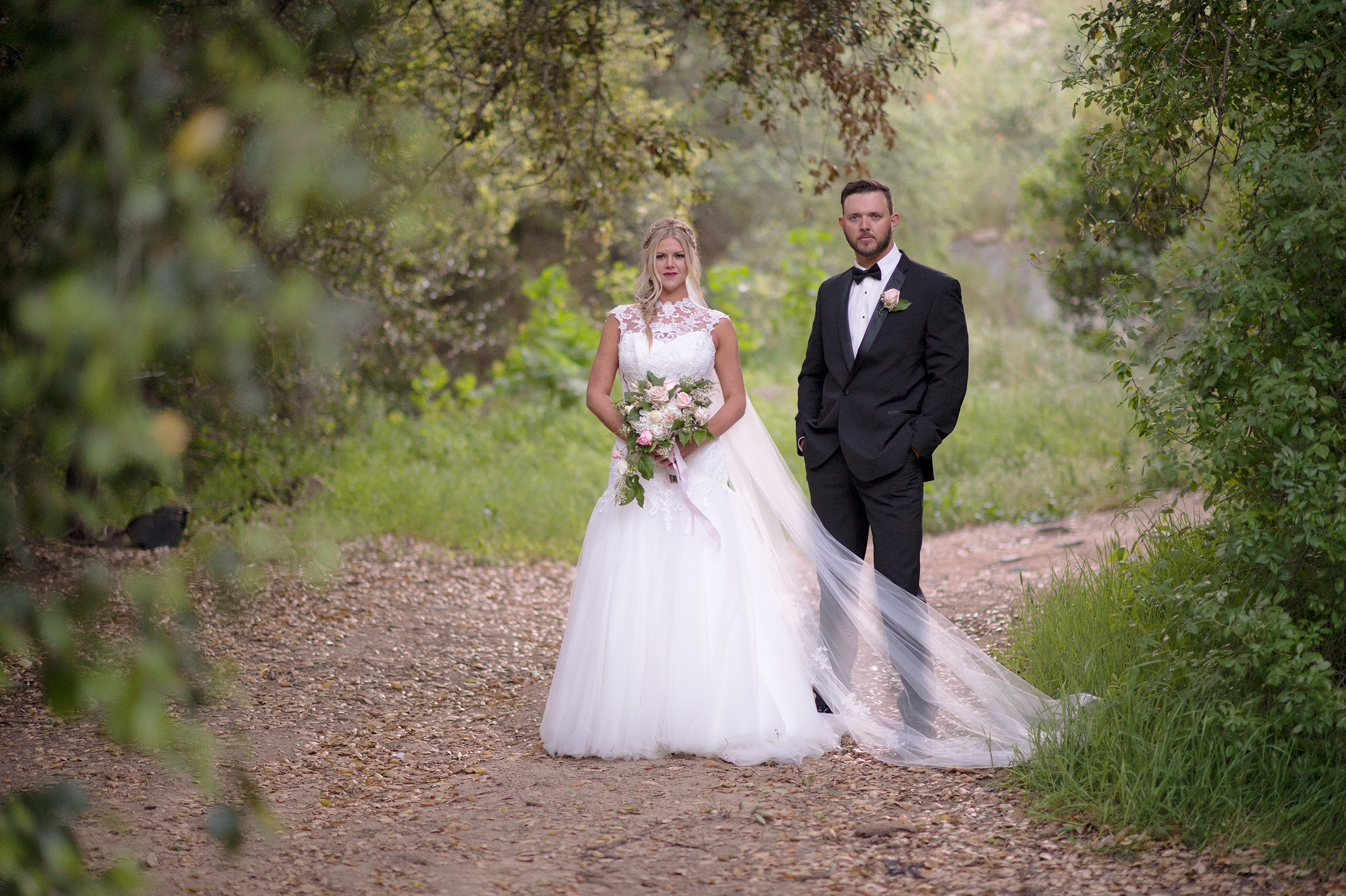 Bride and groom with bouquet at Temecula Creek Inn in Temecula.