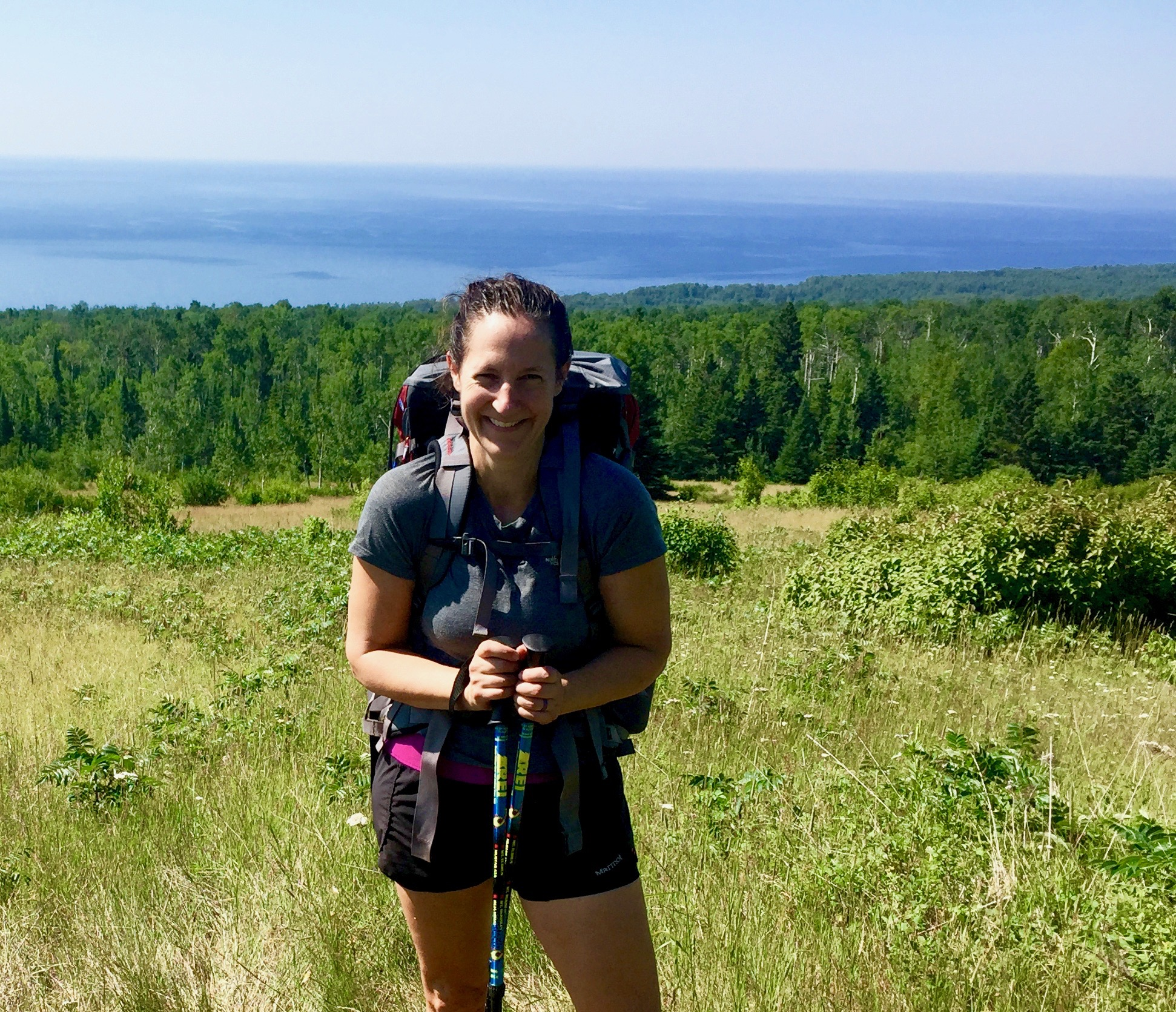 Happy Camper Sarah on Wildflower Hill with a sweeping Lake Superior backdrop.