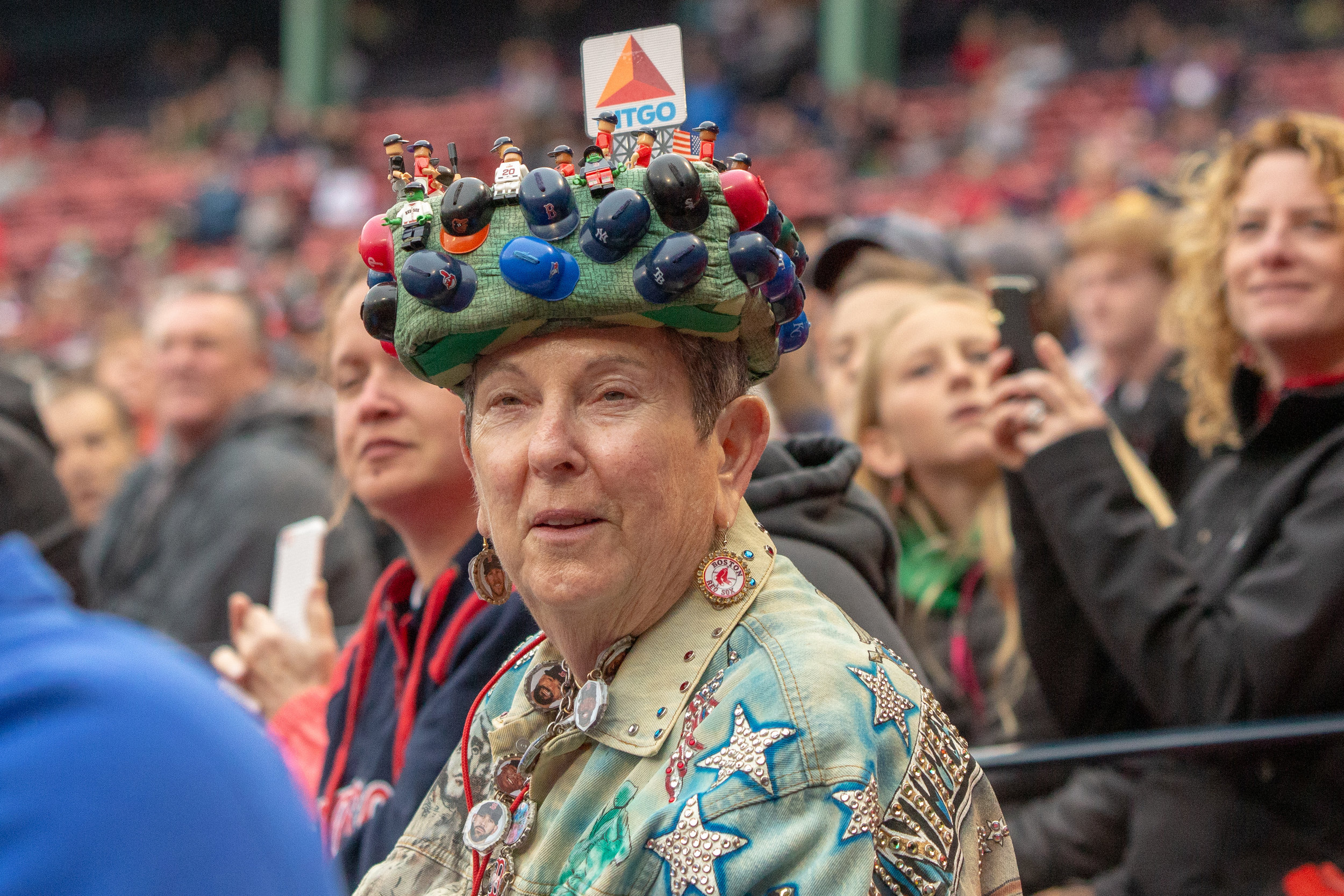 Red Sox super-fan Lynne Smith wears her iconic hat as she watches the 2018 Red Sox Alumni Game. Her hat has a light-up Citgo sign, the game's home team lineup, and a small version of every team's hat.