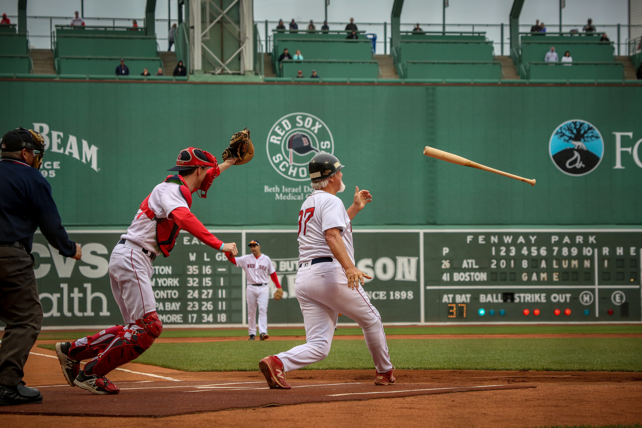 "Bill ""the Spaceman"" Lee, throws his bat forwards during an at-bat at the 2018 Red Sox Alumni Game, wearing an MP helmet in lieu of a traditional batting helmet and in his well-aged New Balances."