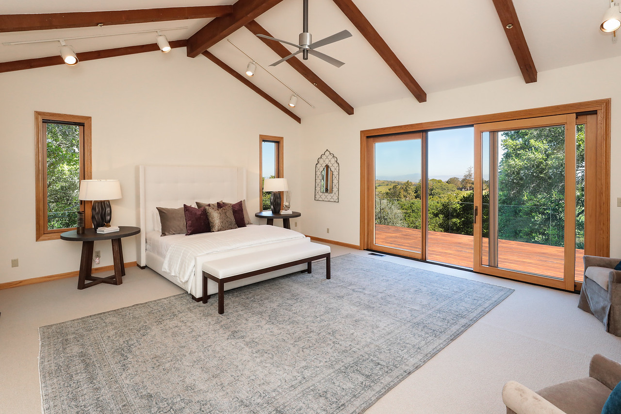 Double doors open to this main-level suite with beamed cathedral ceiling, two cedar-lined walk-in closets, and sliding glass doors to a private deck with sweeping views