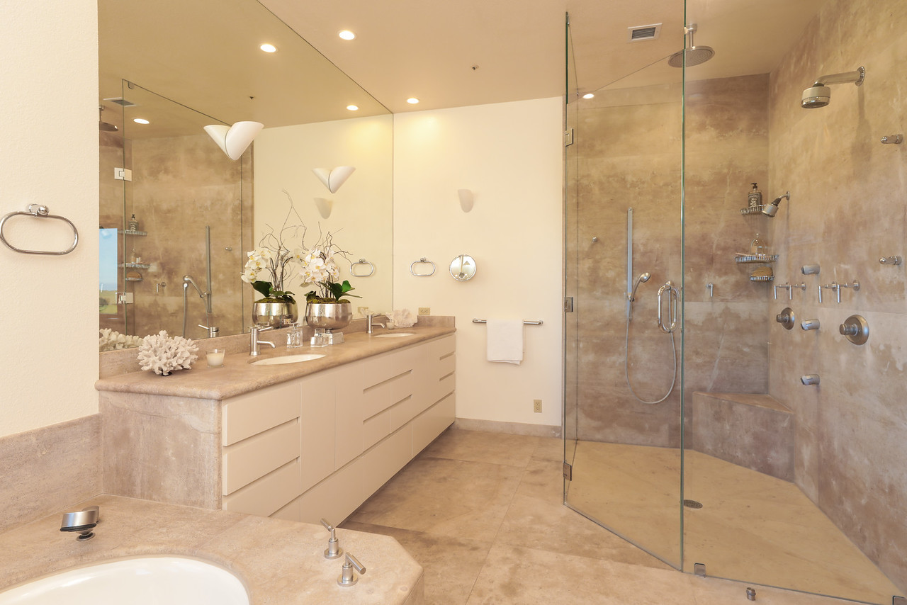 The luxurious limestone bath has a dual-sink vanity, whirlpool tub, and frameless glass-enclosed shower with 7 sprays
