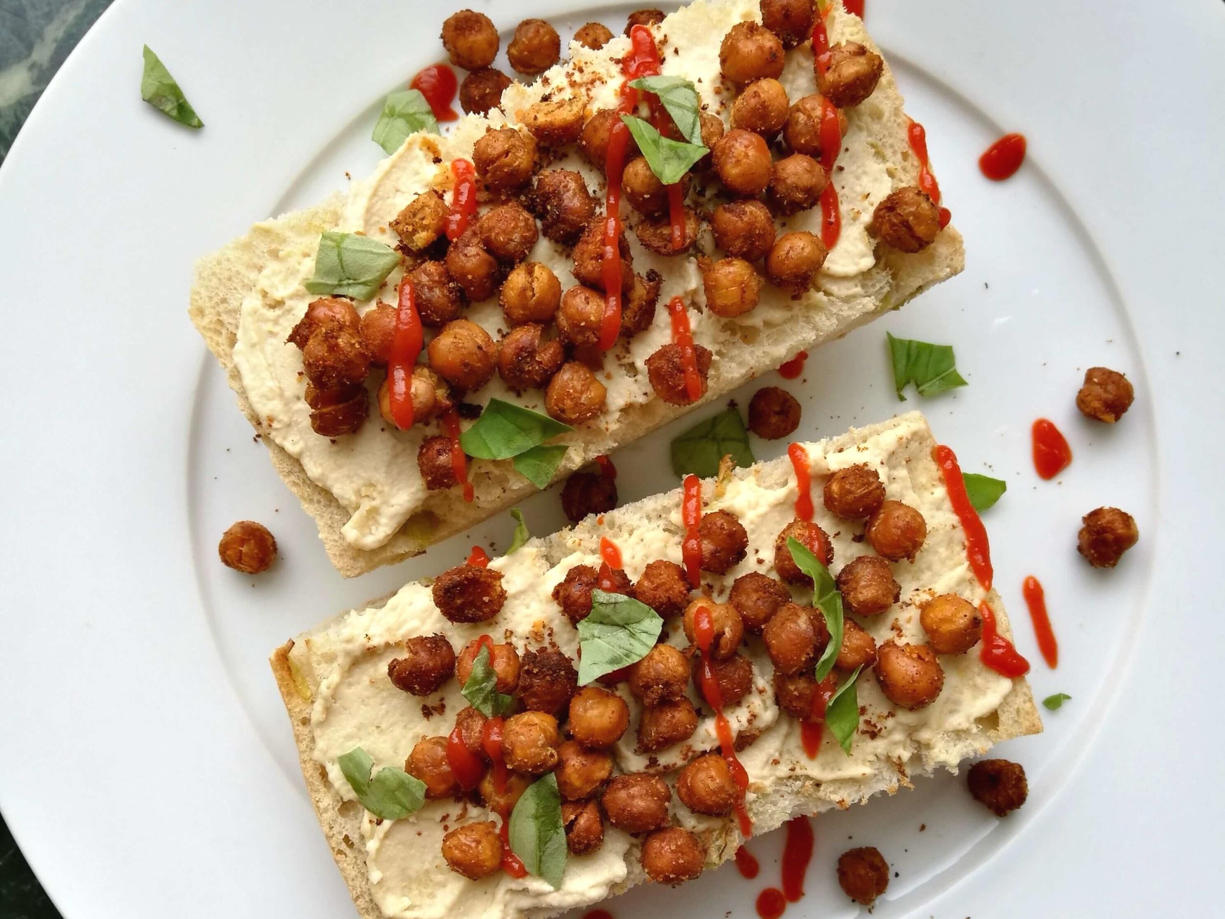 Crispy roasted chickpeas on toast with hummus, sriracha and fresh basil