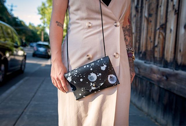 This is one of my hand painted Harvey bags.  They are the perfect little crossbody to keep you hands free, and hold your phone, keys, and wallet.  I keep one in my tote bag and use it when I need to run somewhere really quick or go to an event.  It is minimal, a great size for just the necessities, and the hand painted ones are their own little work of art.  _ These are available in a variety of colors including solid black at @volamos_boutique !! 🖤🖤🖤 . . . . . . . . . . Photography @shawn_hale_photo. . . . . . . . . #makermovement #modernmaker #minimalista #minimaldesign #minimalaesthetic #minimalstyle #minimalluxe #minimallifestyle #minimalaccessories #minimalfashion #leatherclutch #leatherclutchbag #handpainted #handpaintedleather #handpaintedleatherhandbag #streetart #paintdrip #splatter #paintsplatter #Jacksonpollock #mooncycles #celestialdesigns #limitededition #smallbatch #individuallycrafted #handcrafted #craftsmanship #buylocal #shoplocal #shopsmall