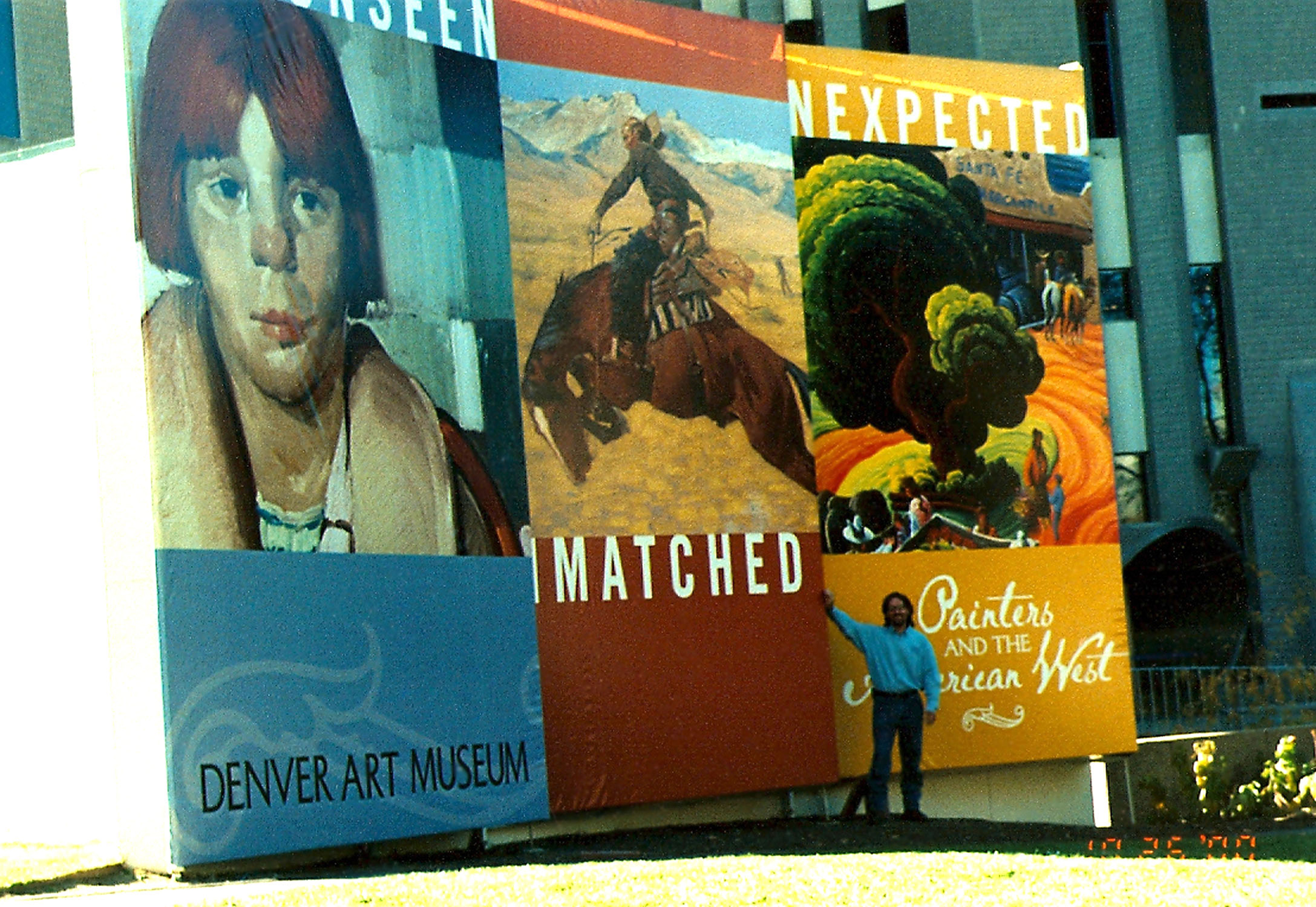 "Kim Wiggins standing in front of the Denver Art Museum at the Painters and the American West Exhibition, 2000.  His painting,  Merging Cultures on the Santa Fe Plaza , is in the background representing the ""Unexpected"" in Western art."