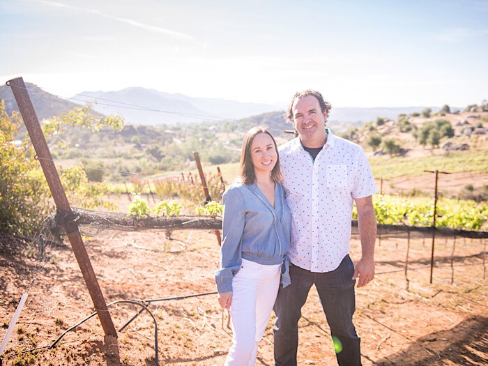 """Emily Towe & Jody Brix Towe - J Brix Wines • San Diego County  After tasting a bottle of Pinot noir grown and made in the Central Coast's Bien Nacido Vineyard, San Diegans Jody and wife Emily got their winemaking start as volunteer harvest interns there, and found they simply couldn't get enough of the dirty work. One dream led to another; J. Brix Wines is the unexpectedly felicitous result.  Jody's college and career background in horticulture translates to time and study in the vineyards; there's nowhere he'd rather be. A keen understanding of plant physiology provides insight into the way each individual growing season affects the vines, the fruit, and the wine. A keen intuition built on many years working with plants helps guide winemaking decisions, which vary from harvest to harvest based on the sum of the season.He drives a lot.  Emily is fascinated by stories. Along the way, she's found herself caught up in one of her own. Every winemaking year provides a new and unscripted tale to tell, and as a writer and designer, she finds great joy in the translation: written, graphic and vinous.  She and Jody have come to view their lives in two phases: the one before they spoke those three little words ( """"Let's make wine""""),  and the one that has followed. Subsequent adventures have been more thrilling, and fulfilling, than anything she ever could have imagined. Electric mayhem? Absolutely. Heartbreak? Occasionally. In the fleeting moments, though, it's all nothing short of magical."""