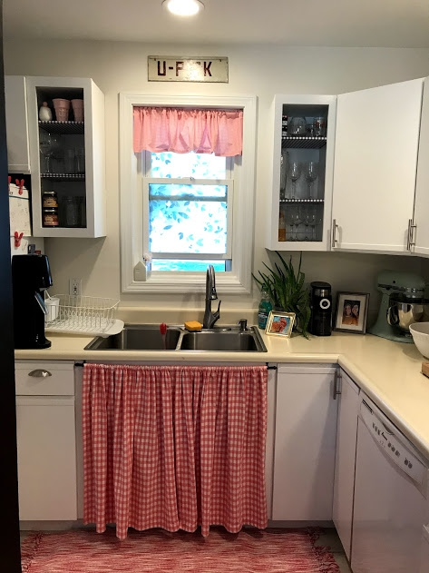The new faucet and sink look great, but so do the now open shelves on either side of the window! And removing the doors under the sink to add a skirt gives the kitchen some modern-farmhouse flair!