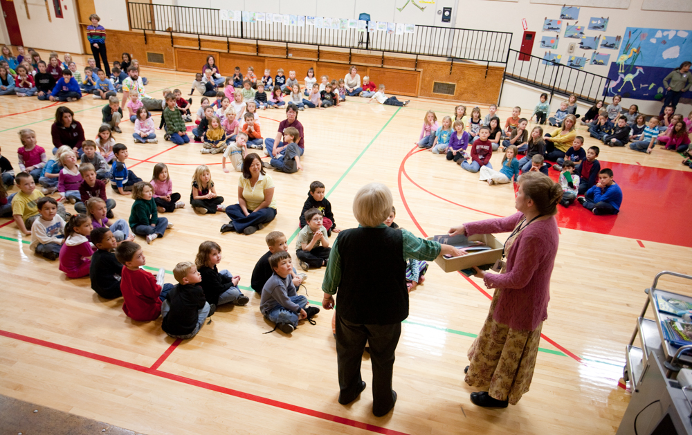 """Kindergarten through third grade students from Hawthorne Elementary listen attentively as Love gives a presentation on Herons. The students have been reading her book, """"Henry the Impatient Heron."""" Three students were picked to receive a free copy of the book."""