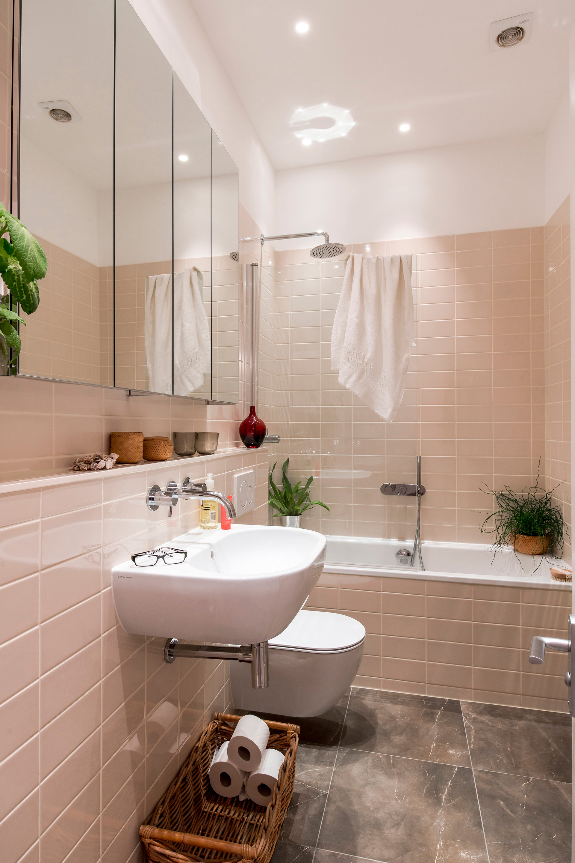 Family bathroom with glossy ref;ective tiles and good lighting to make the space feel light and airy. Storage cubbies and shelf were introduced for extra family storage of bath toys and toiletries.