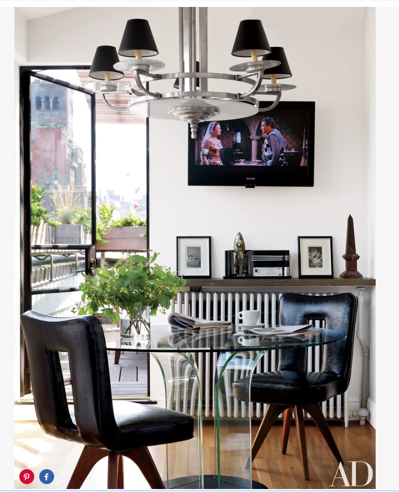 The kitchen's dining area is outfitted with an Art Deco chandelier and a vintage table and chairs.