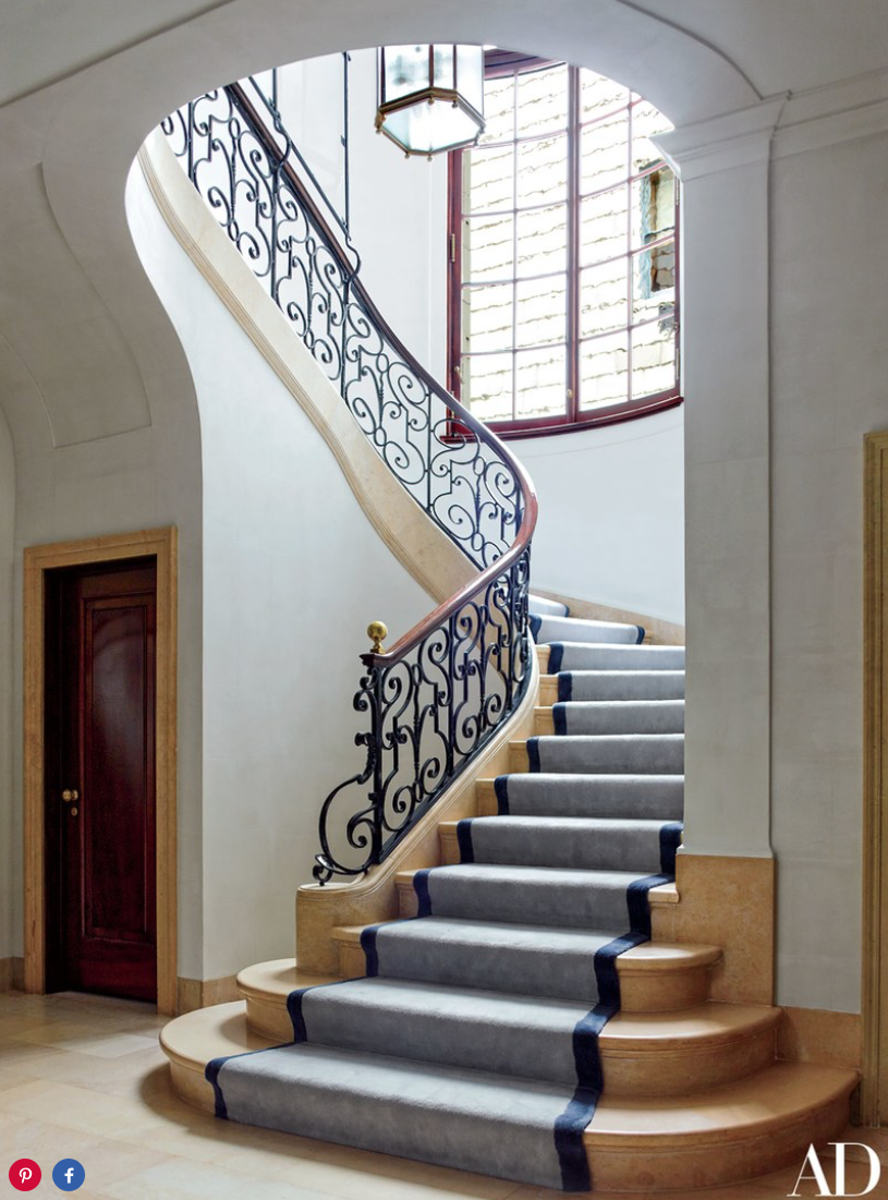 The staircase, showcasing its original 1912 balustrade, is softened by a Beauvais runner.