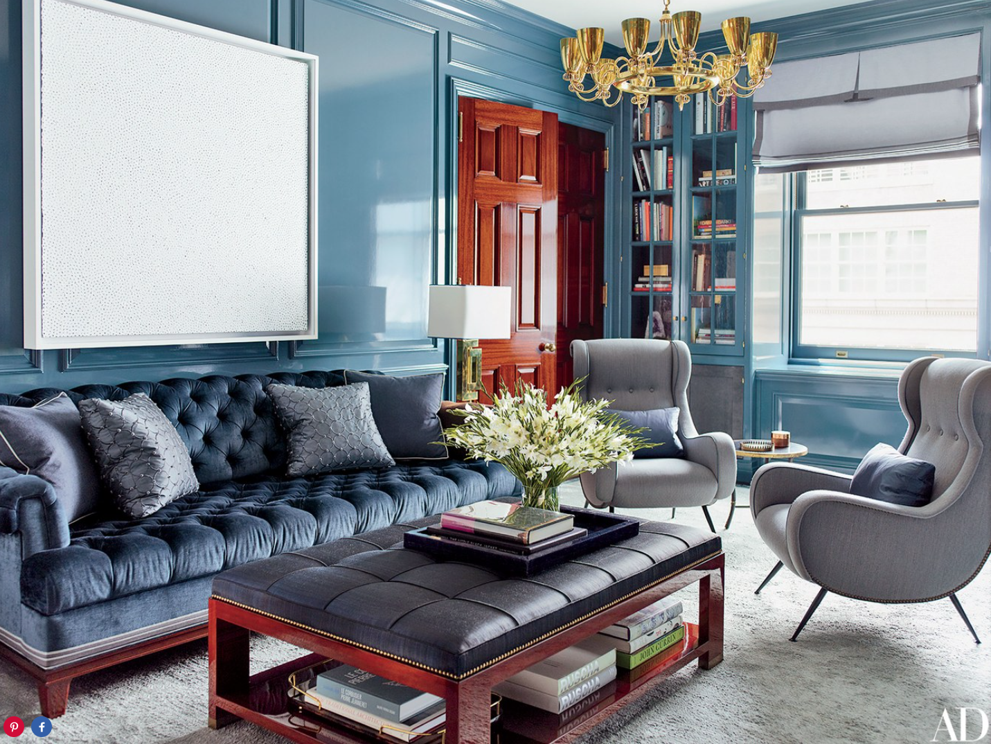 Walls painted in a Sherwin-Williams high-gloss oil serve as the backdrop for a Yayoi Kusama canvas in the library; the sofa is upholstered in a Robert Allen velvet, and the armchairs are vintage Paolo Buffa designs.