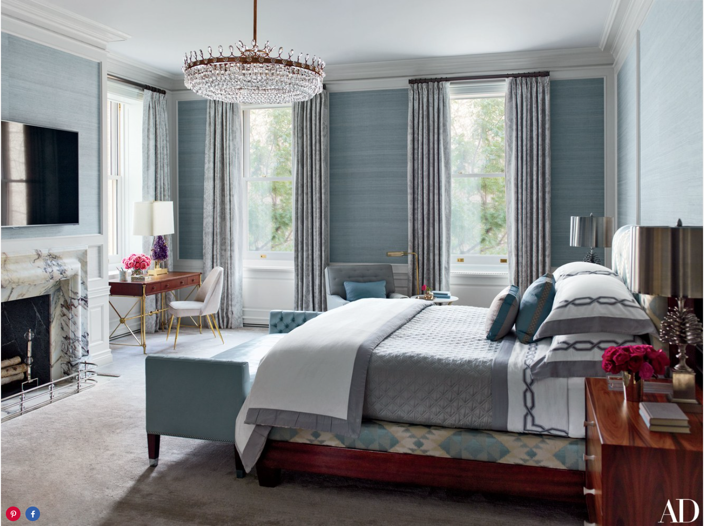 Designed by S. R. Gambrel and crafted by Dune, the master suite's mahogany bed is upholstered in an Old World Weavers fabric and dressed with custom-made bedding by E. Braun & Co.; the curtains are of a de Le Cuona fabric, and a Samsung television is over the fireplace.