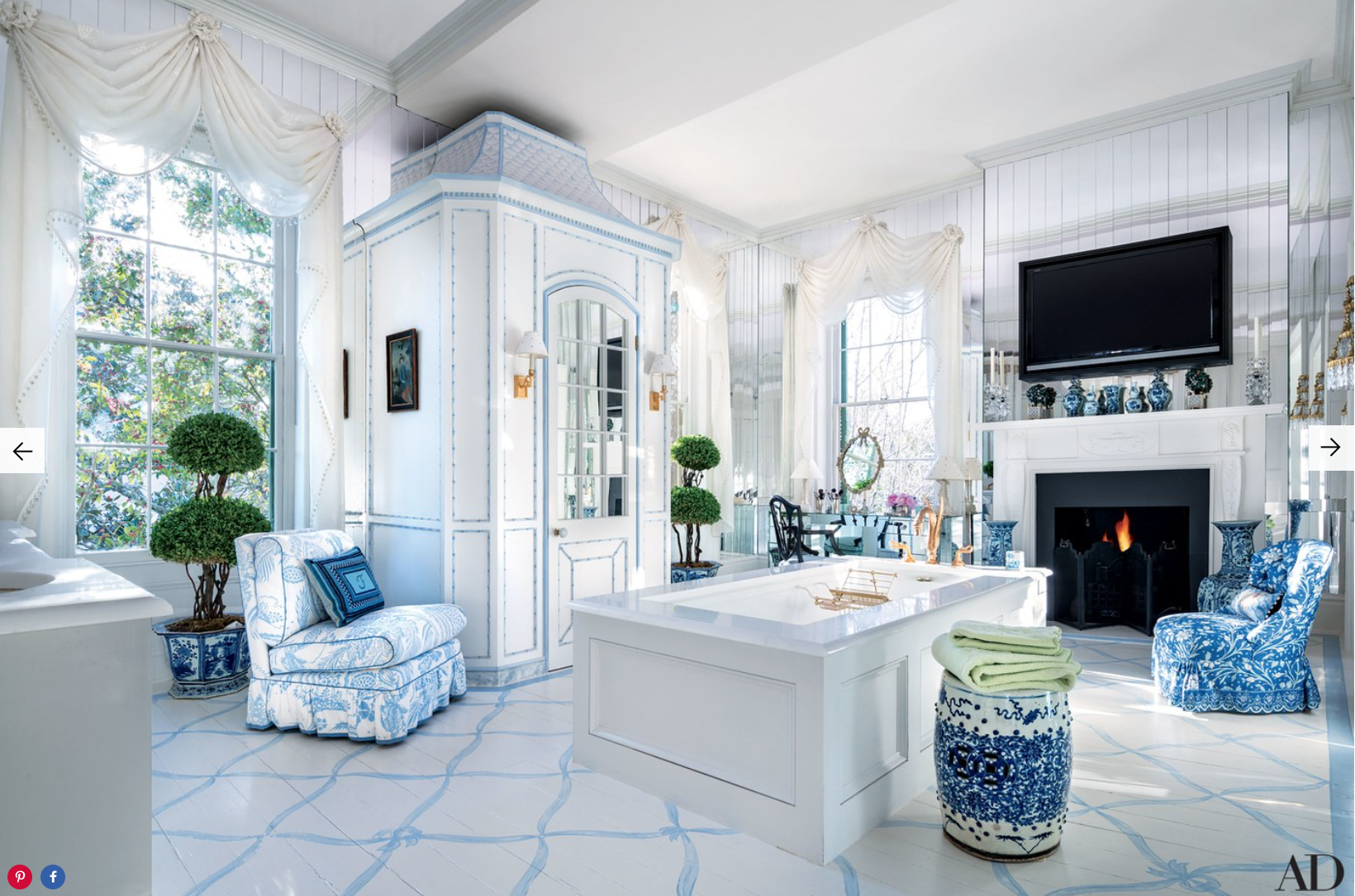 In the master bath, the toilet is concealed in a tall chinoiserie cabinet; a Manuel Canovas print covers the slipper chair at left, a Brunschwig & Fils fabric was used on the chair at right, and the garden stool is from John Rosselli Antiques.