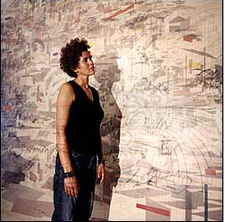 The Artist : Julie Mehretu in front of a work-in-progress. She makes her large paintings by projecting one of her drawings onto a canvas, then tracing the lines. (Photo: Joseph Maida)