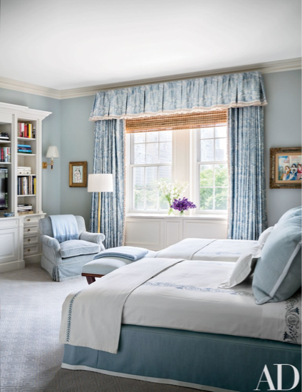 The room is painted in a Farrow & Ball blue, with curtains of a Brunschwig & Fils fabric; the floor lamp is from Karl Kemp Antiques, and the bedding is by Leontine Linens.