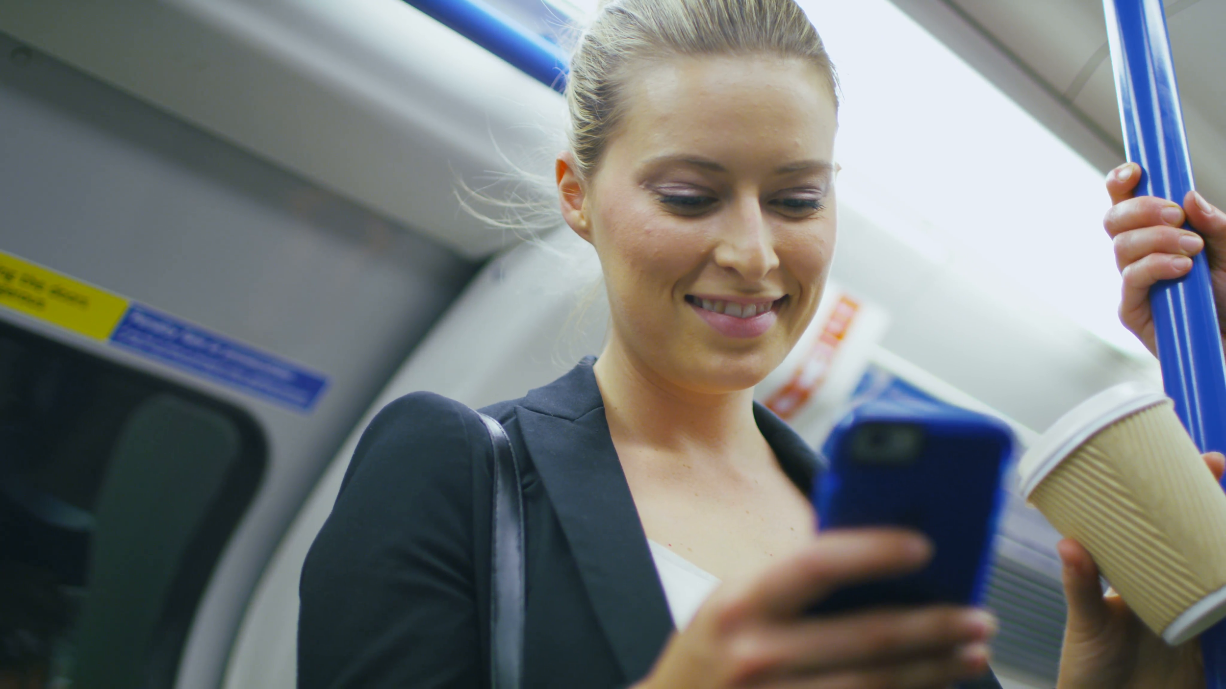 4k-attractive-business-woman-standing-on-a-train-drinking-from-a-coffee-cup-whilst-reading-her-phone-in-slow-motion-shot-on-red-epic_4jtrflla__F0011.png