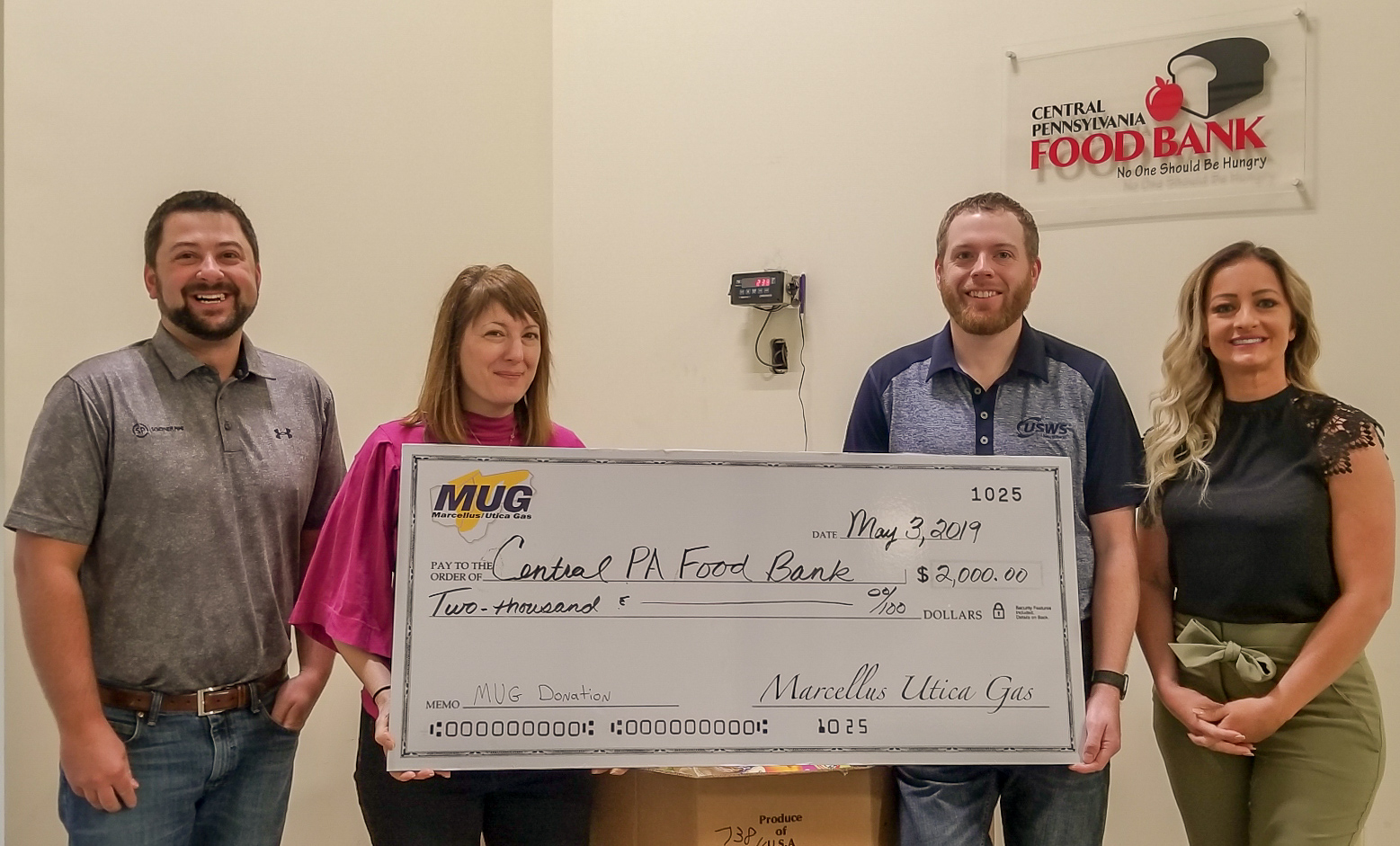 Marcellus & Utica Gas Suppliers, Services, and Manufacturers Association (MUG) Board Members Zane Johnson (Sooner Pipe), Chris LaBarte (US Well Services), and Crystal Miller (Silver Creek Services) present a check and a 325 pound food donation to the Central Pennsylvania Food Bank in Williamsport, PA.