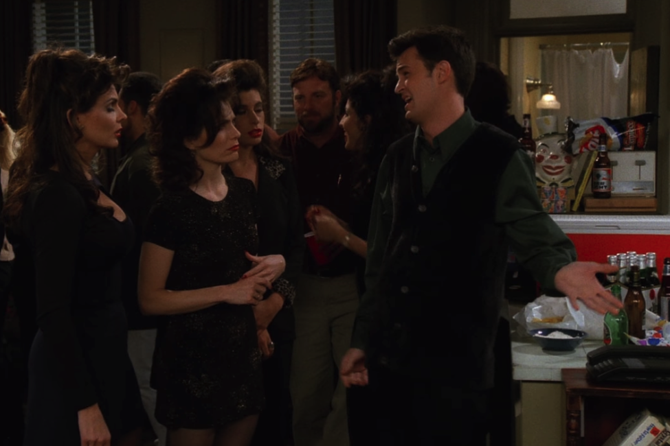 Chandler talking to a couple of Joey's sisters at Joey's birthday party / NBC Universal / Handbag Marinara: A Friends TV Show Podcast / @handbagmarinara