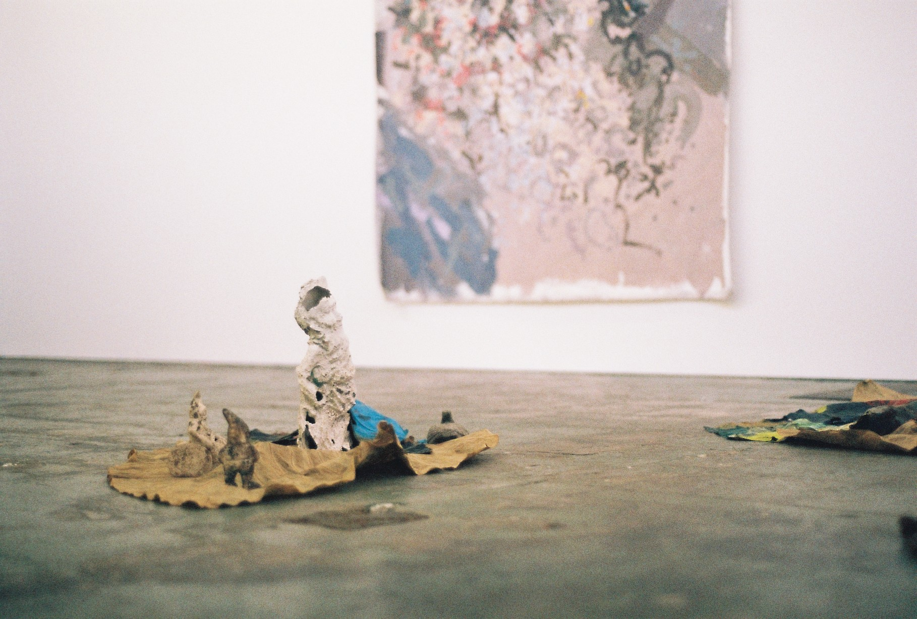 Foreground: Alice McIntosh,  Leaves ft. Figures , 2018 found figurines, leaves, oil paint Background: Gian Manik,  Untitled (Pacific Oysters) , 2017 aerosol and acrylic on canvas