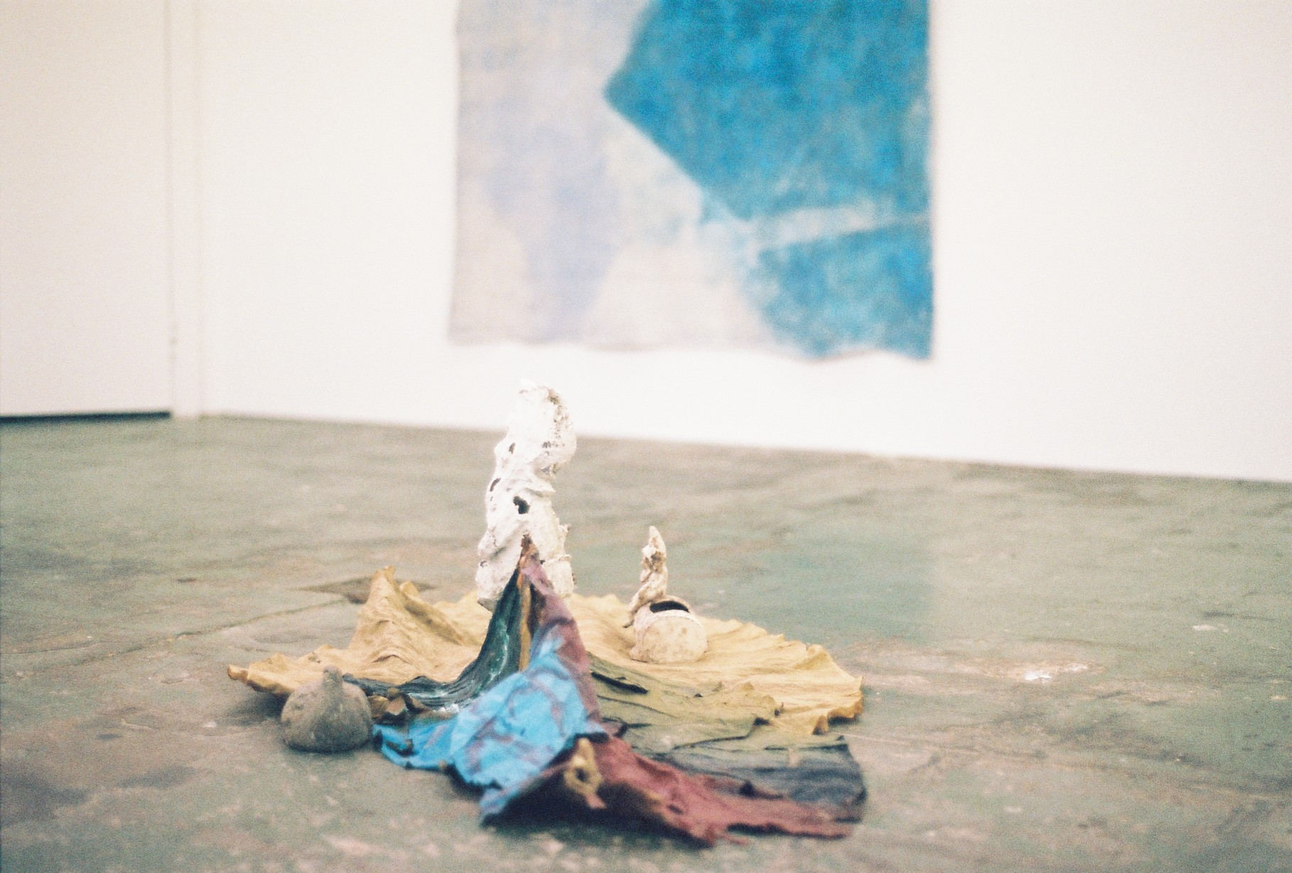Foreground: Alice McIntosh,  Leaves ft. Figures , 2018 found figurines, leaves, oil paint Background: Jahnne Pasco–White,  The bluest feet around , 2017 ash, limestone, PVA, pigment, spray adhesive, acrylic on cotton courtesy Daine Singer, Melbourne