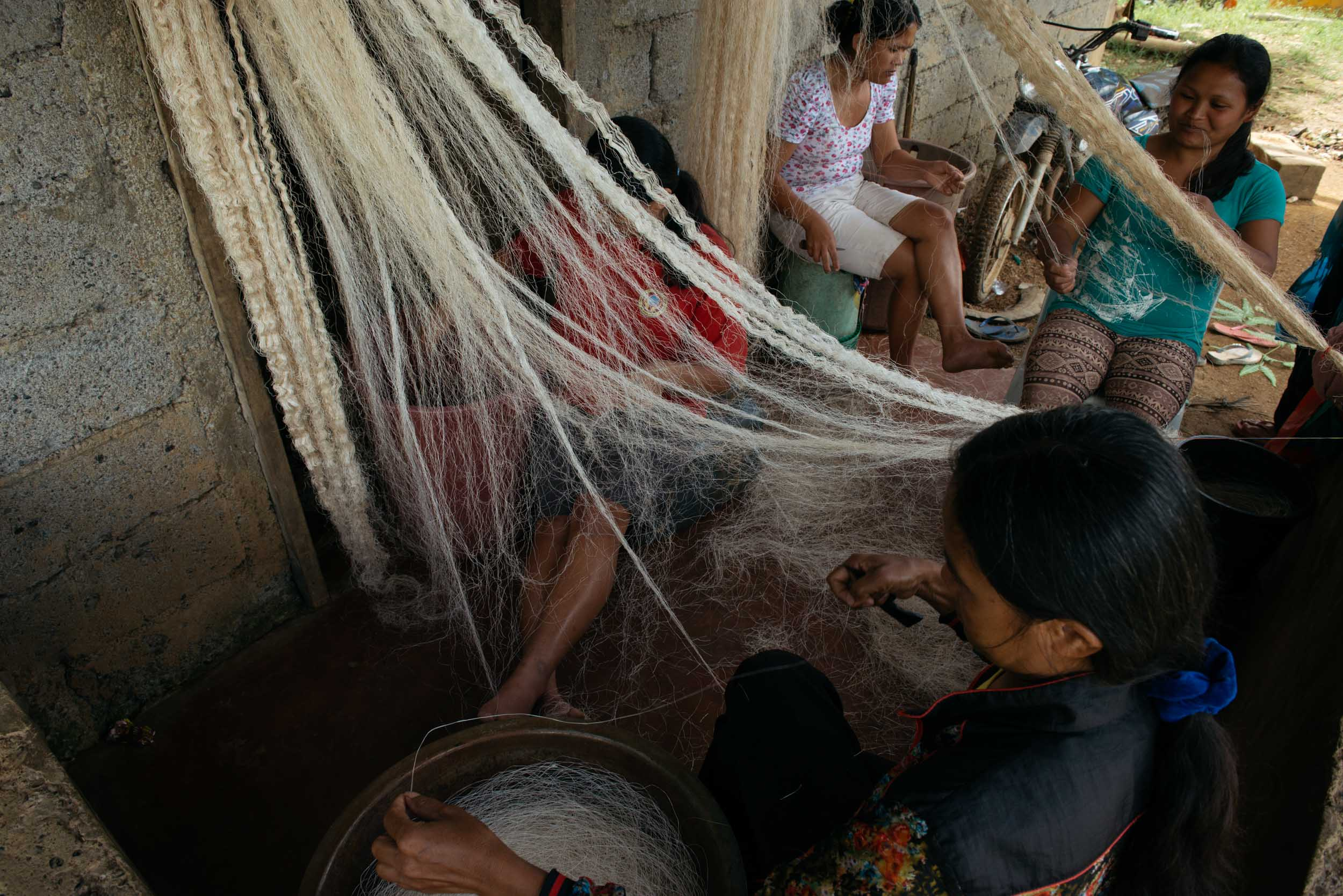 The women from the community will then start their afternoons with a side of daily chats and catch-ups through  pagkukuyakay  or choosing strands of fiber from a hanged freshly sun-baked  lanot . By  pagkuyakay , they patiently combine two or three fibers together to create meters of threads for weaving. Along with  pagkuyakay  is the  pagdugtong  or knotting of lanot to create longer threads.