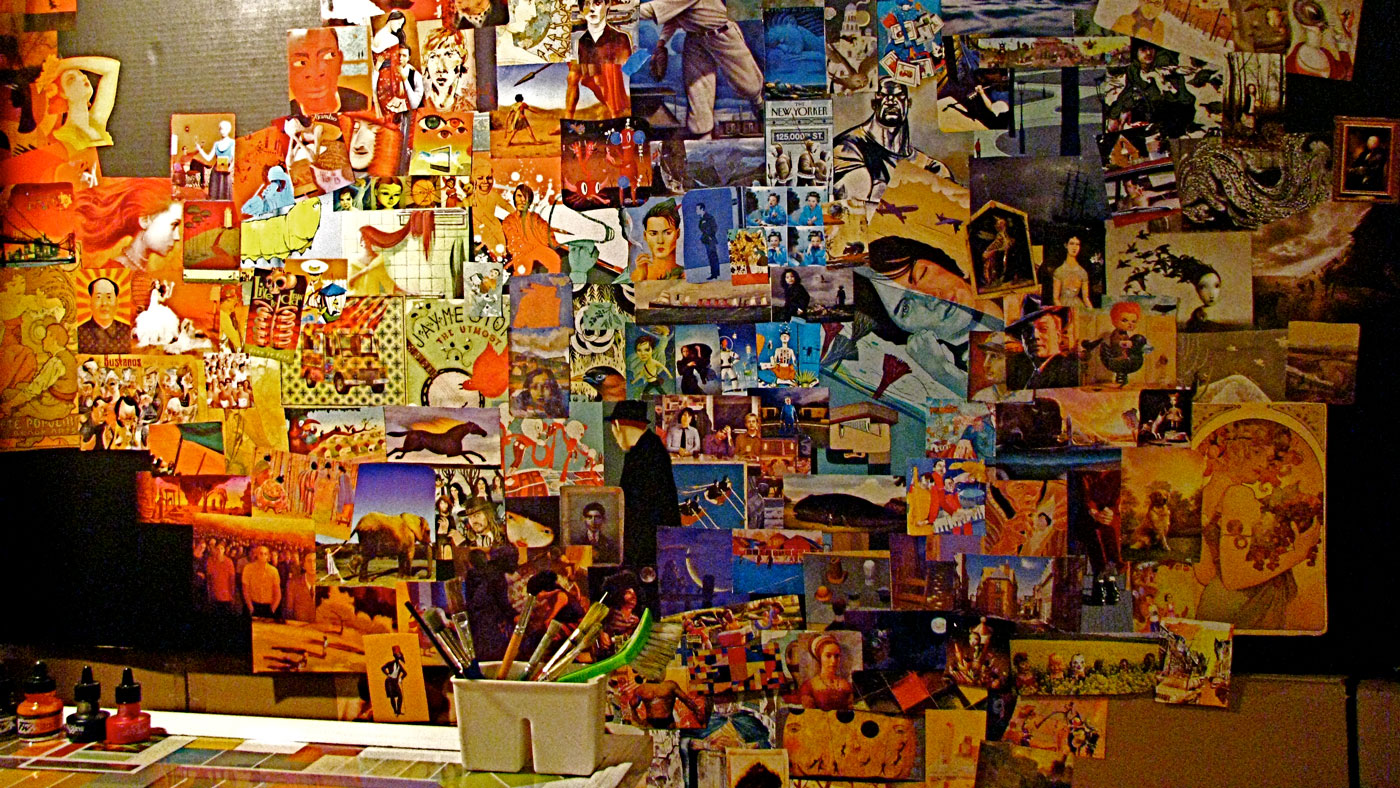 Artist's studio with colourful paintings on walls and art materials on floor