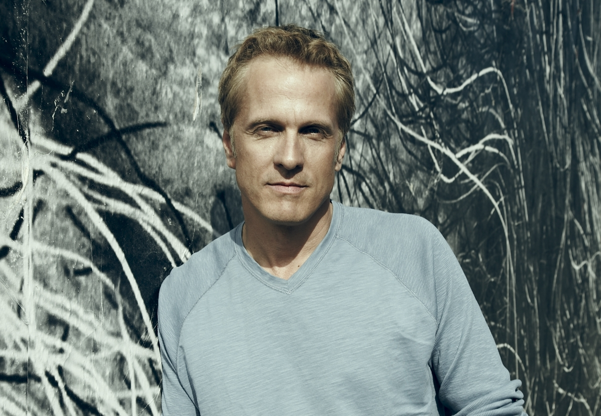 Actor Patrick Fabian leaning against wall with graffiti