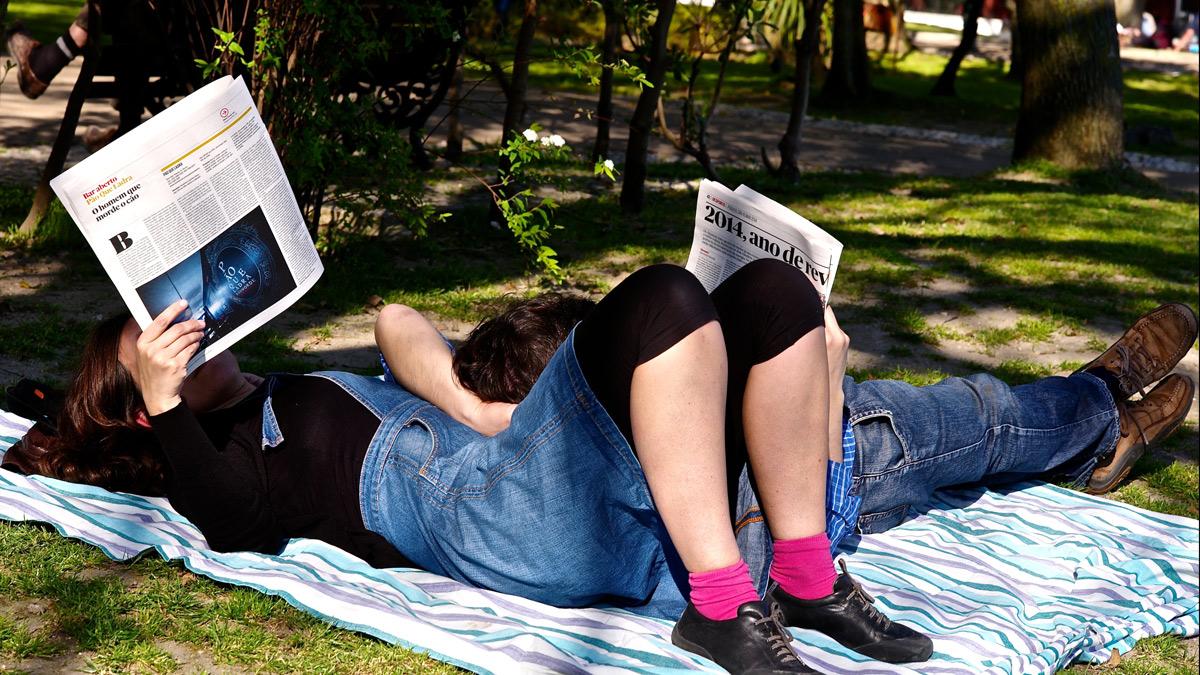 People lying on blanket in park reading newspapers